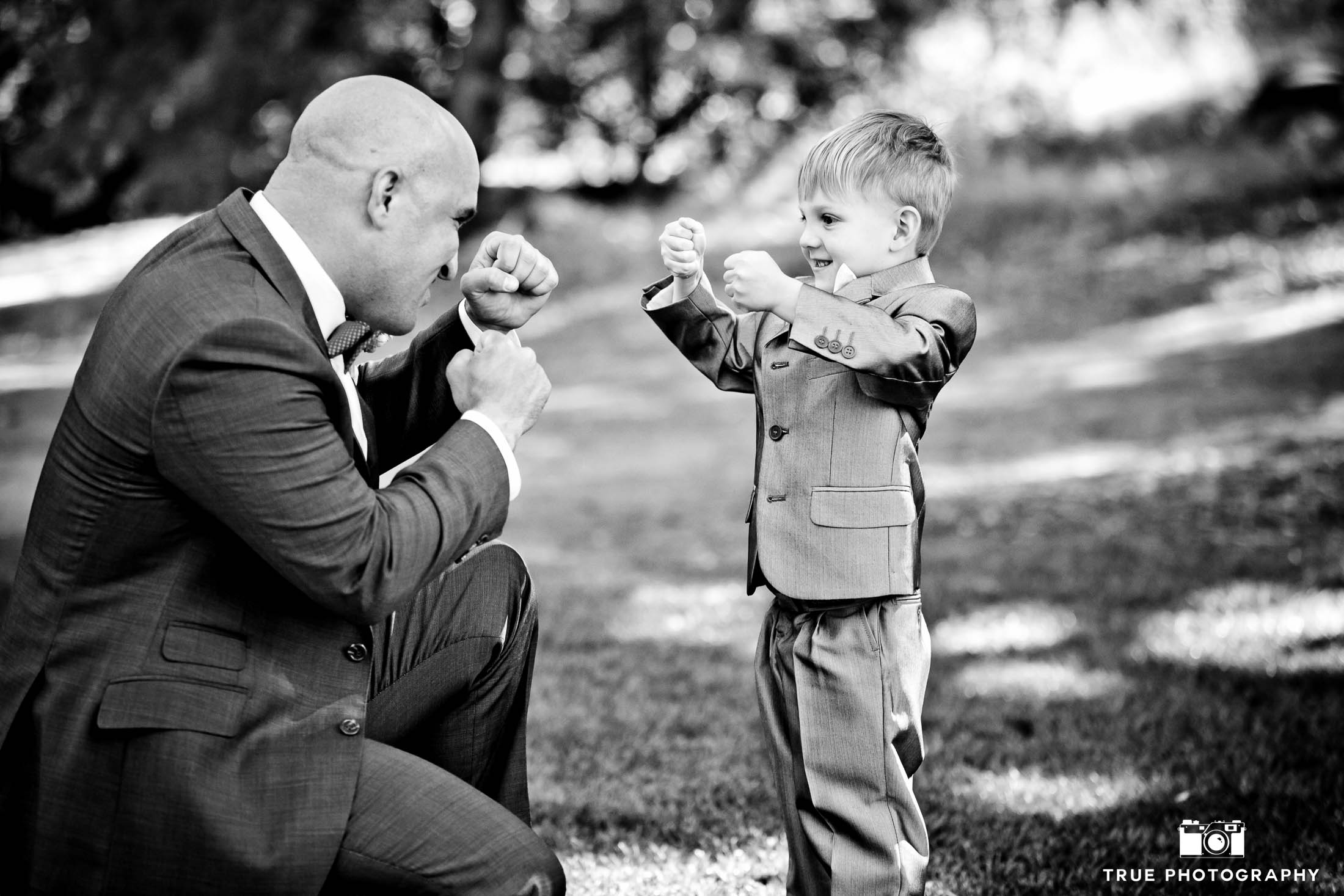 Cute moment with Groom play-fighting with young boy before wedding ceremony