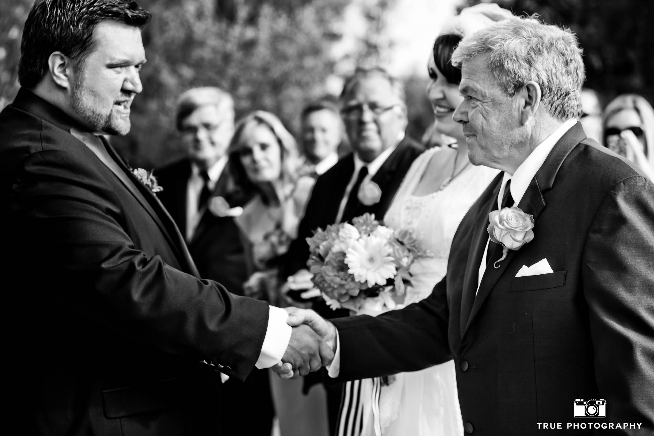 Bride's Dad shakes Grooms hand after walking daughter down wedding aisle