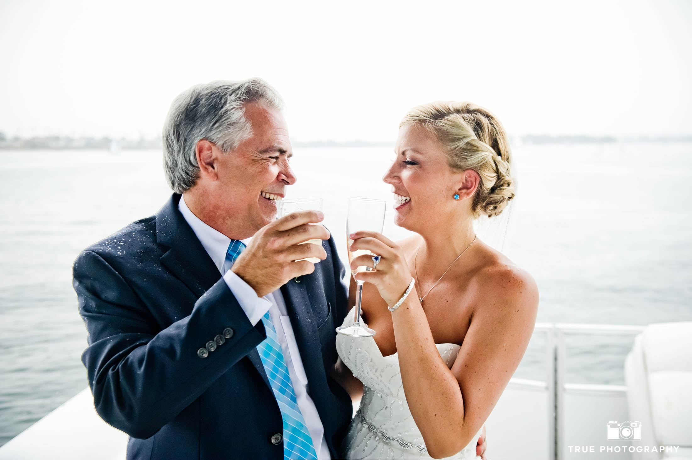 Bride laughs with Father as they share toast after wedding ceremony