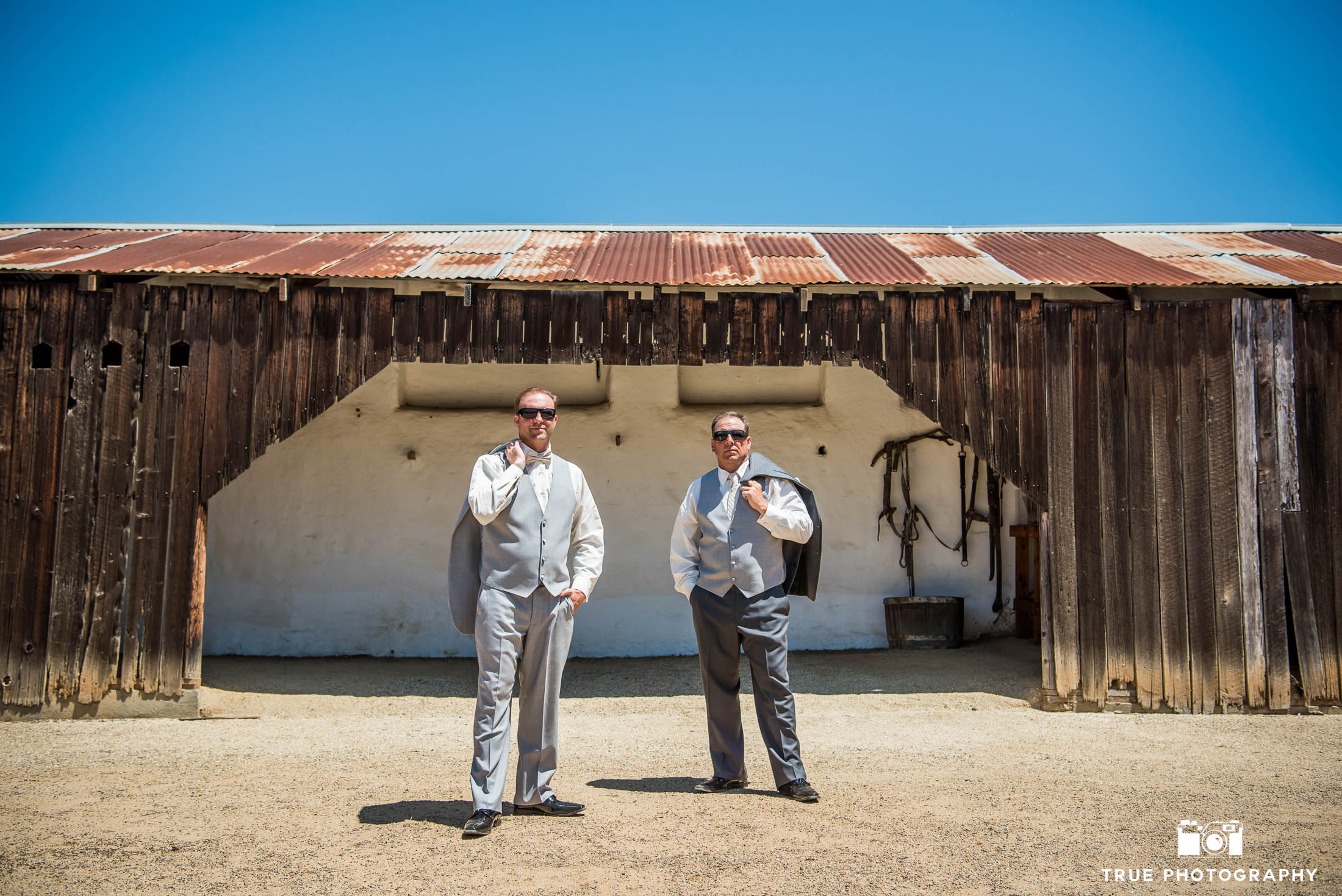 Groomsmen portraits with jackets off at rustic, spanish-style barn