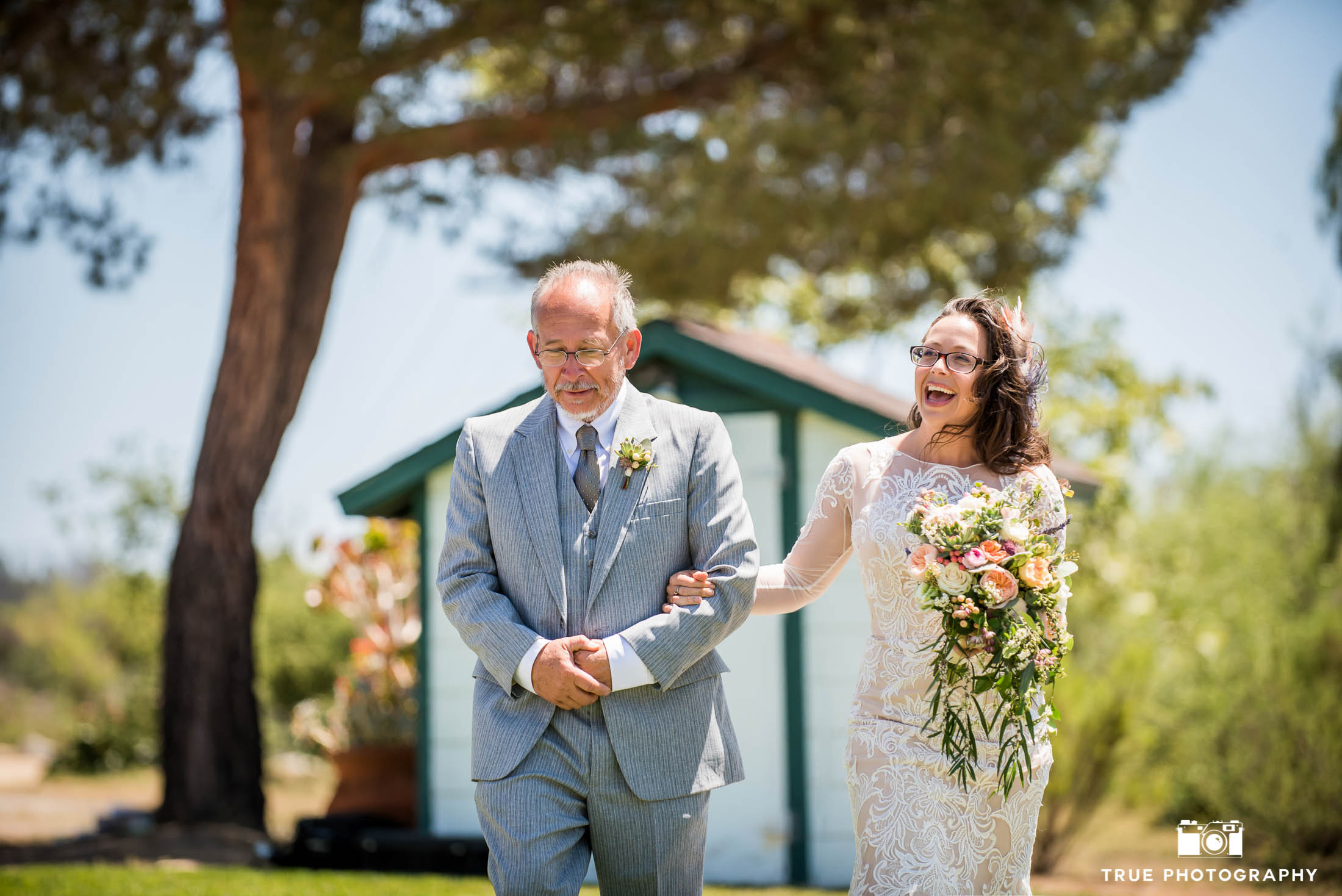 Bride and Father walk down aisle during outdoor rustic wedding in Vista