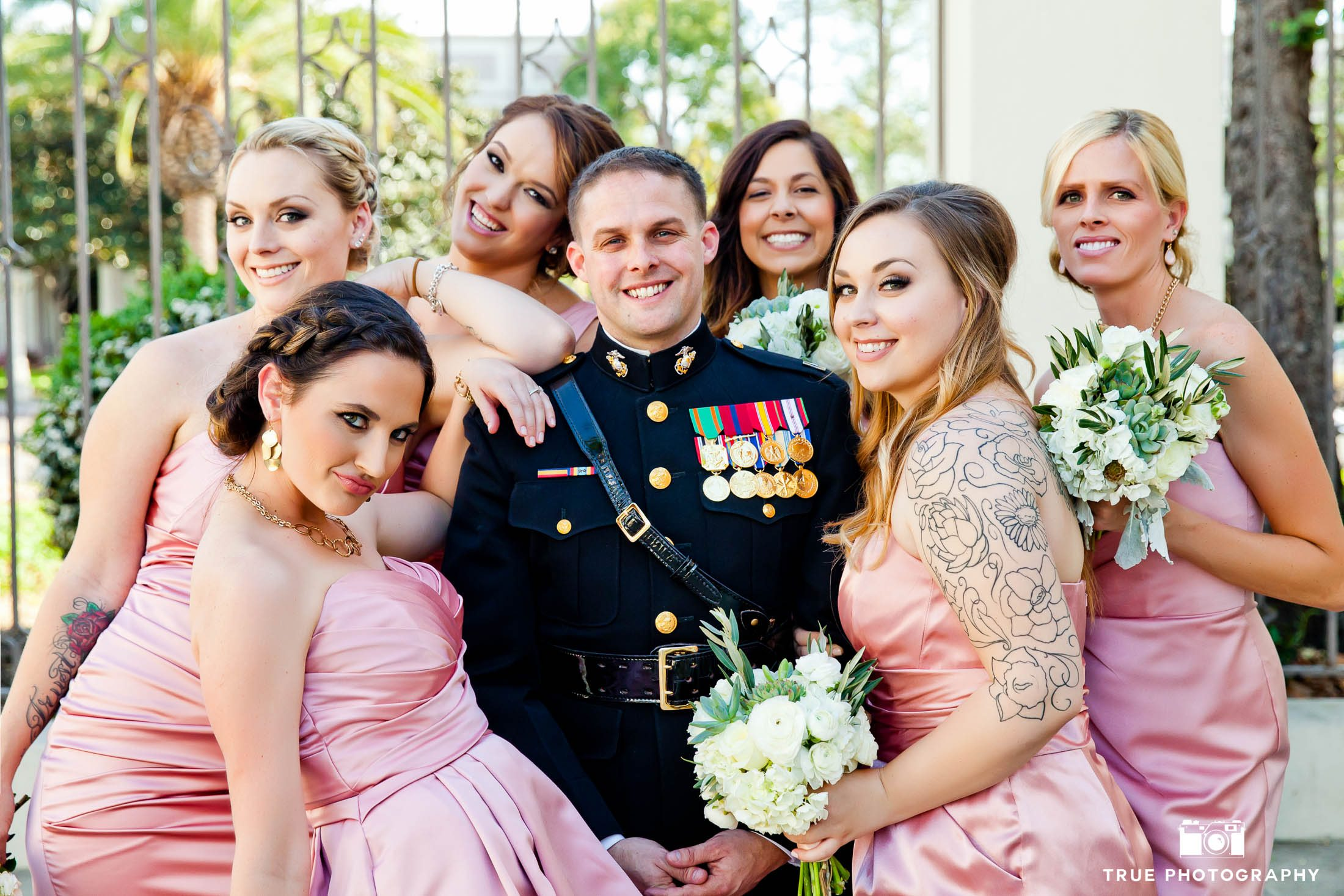 Military Groom poses with group of Bridesmaids before wedding ceremony