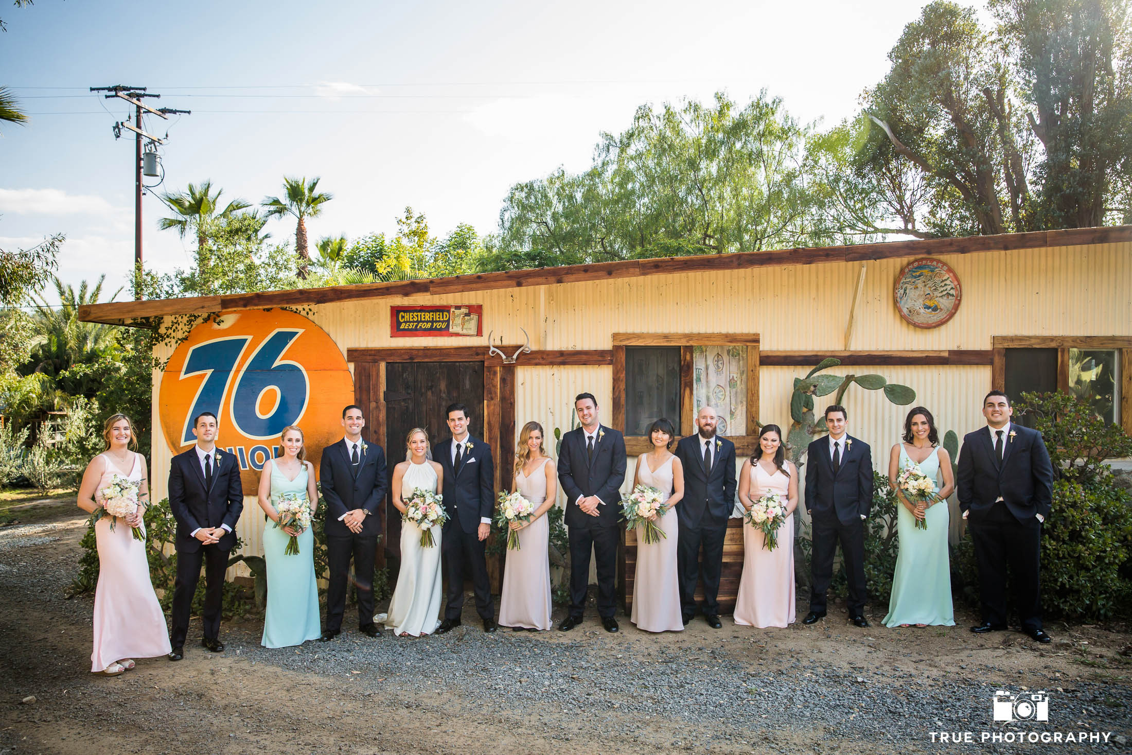 Bohemian modern wedding bridal party outside vintage 76 gas station