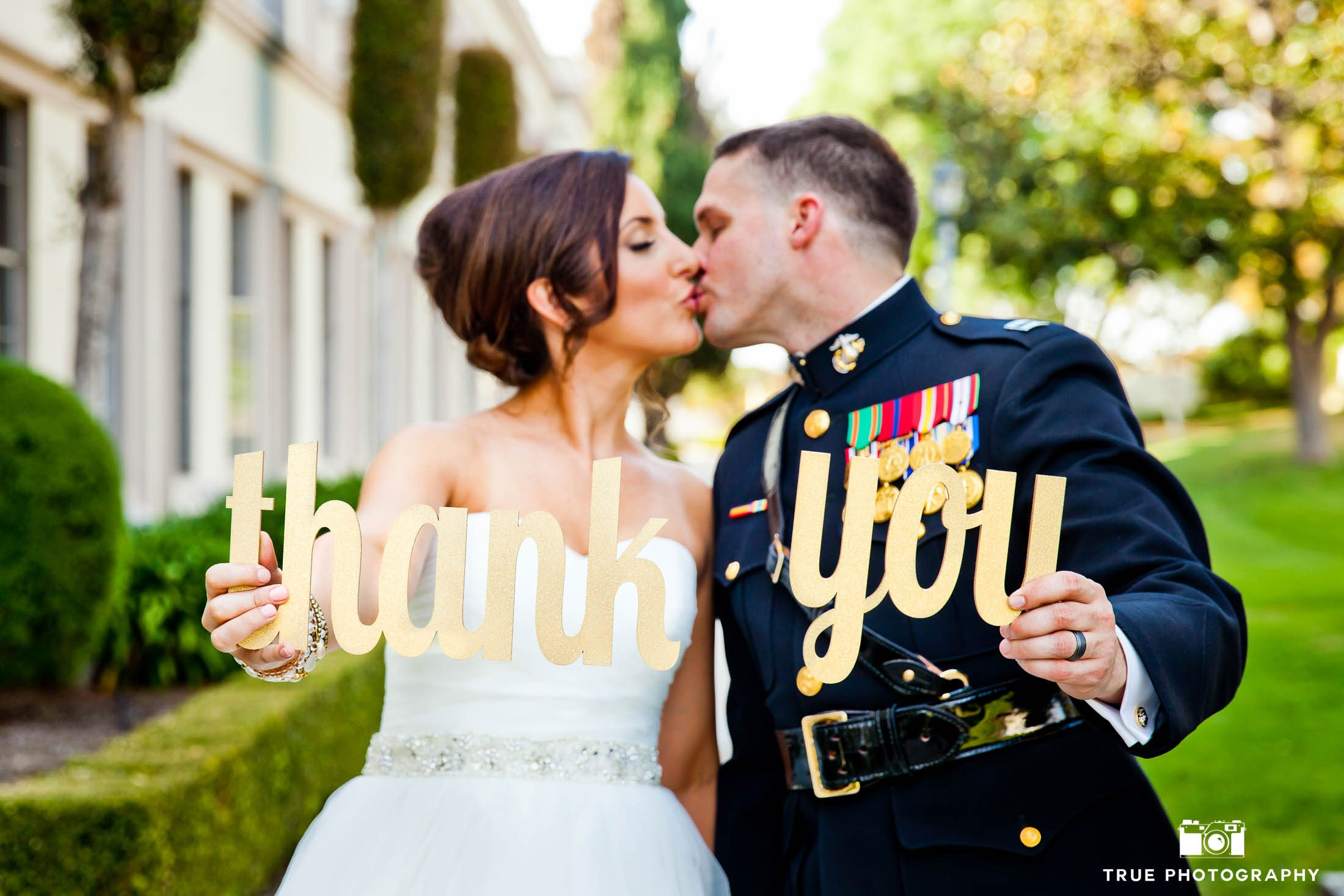 Military Groom in Uniform kisses Bride as they hold Thank you Sign