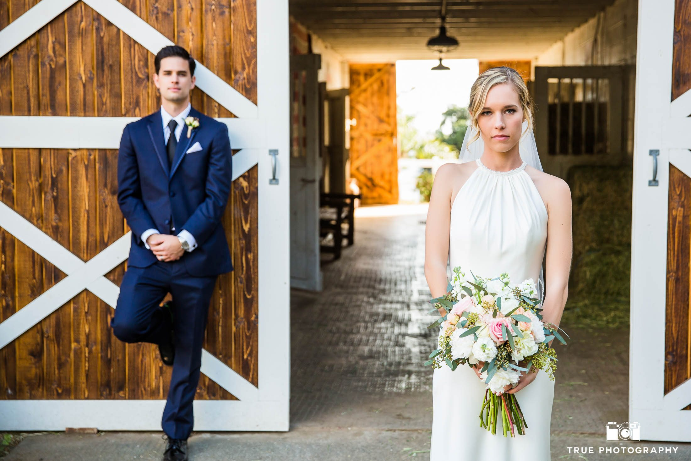 Bride and Groom stand in front of rustic barn door after outdoor ceremony