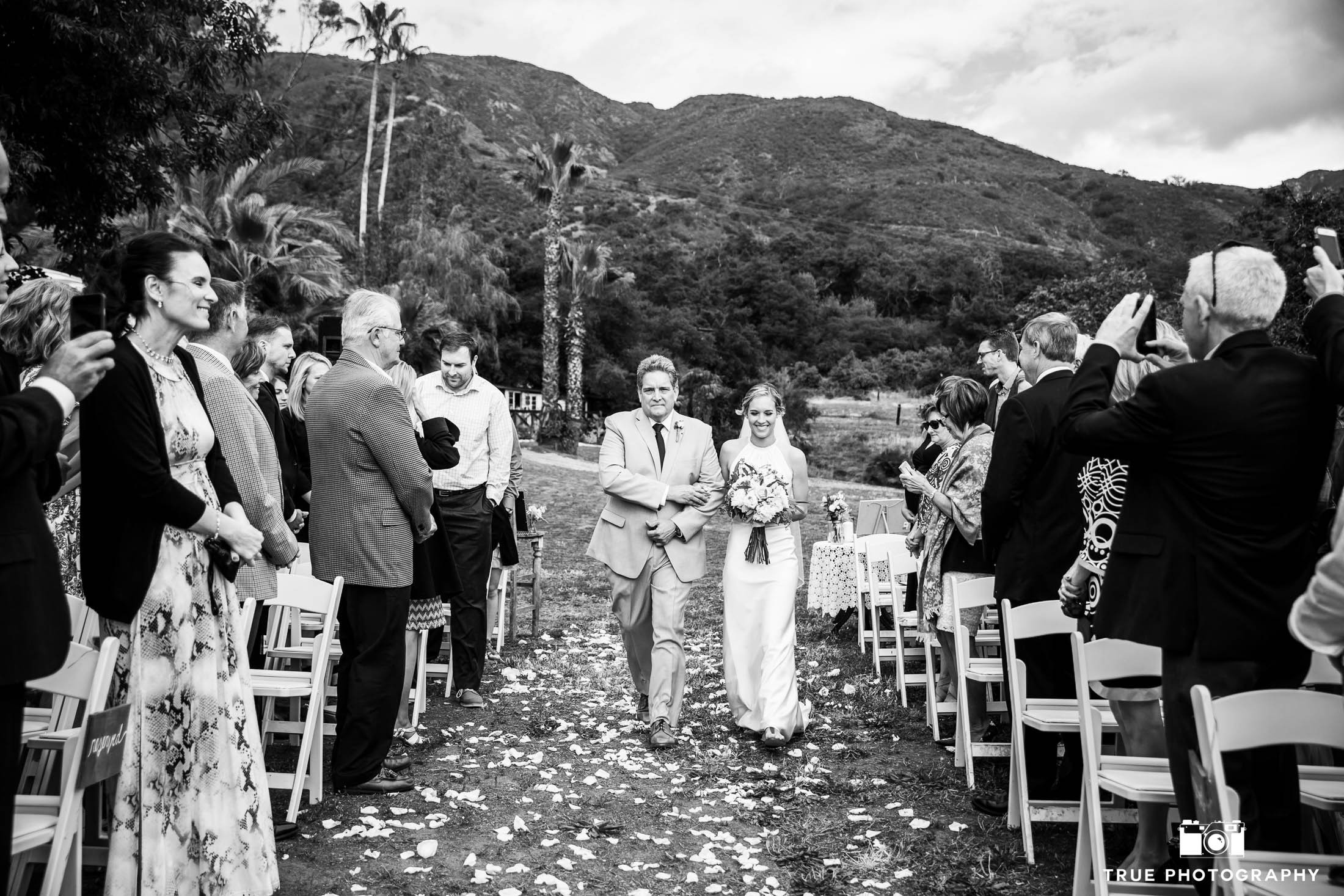Father walks Bride down flower aisle during wedding ceremony