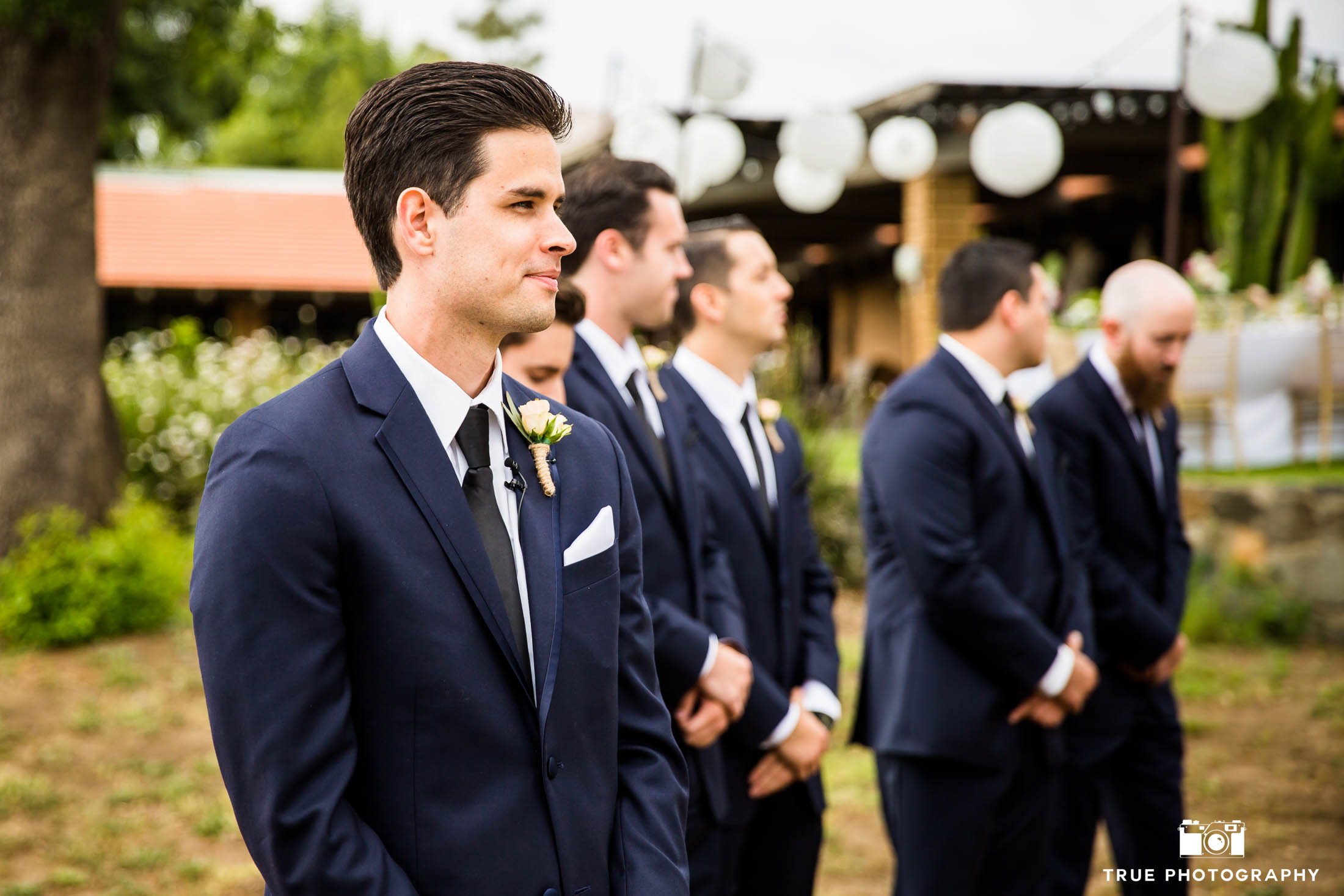 Groom looks on and smiles after seeing Bride come down aisle during wedding