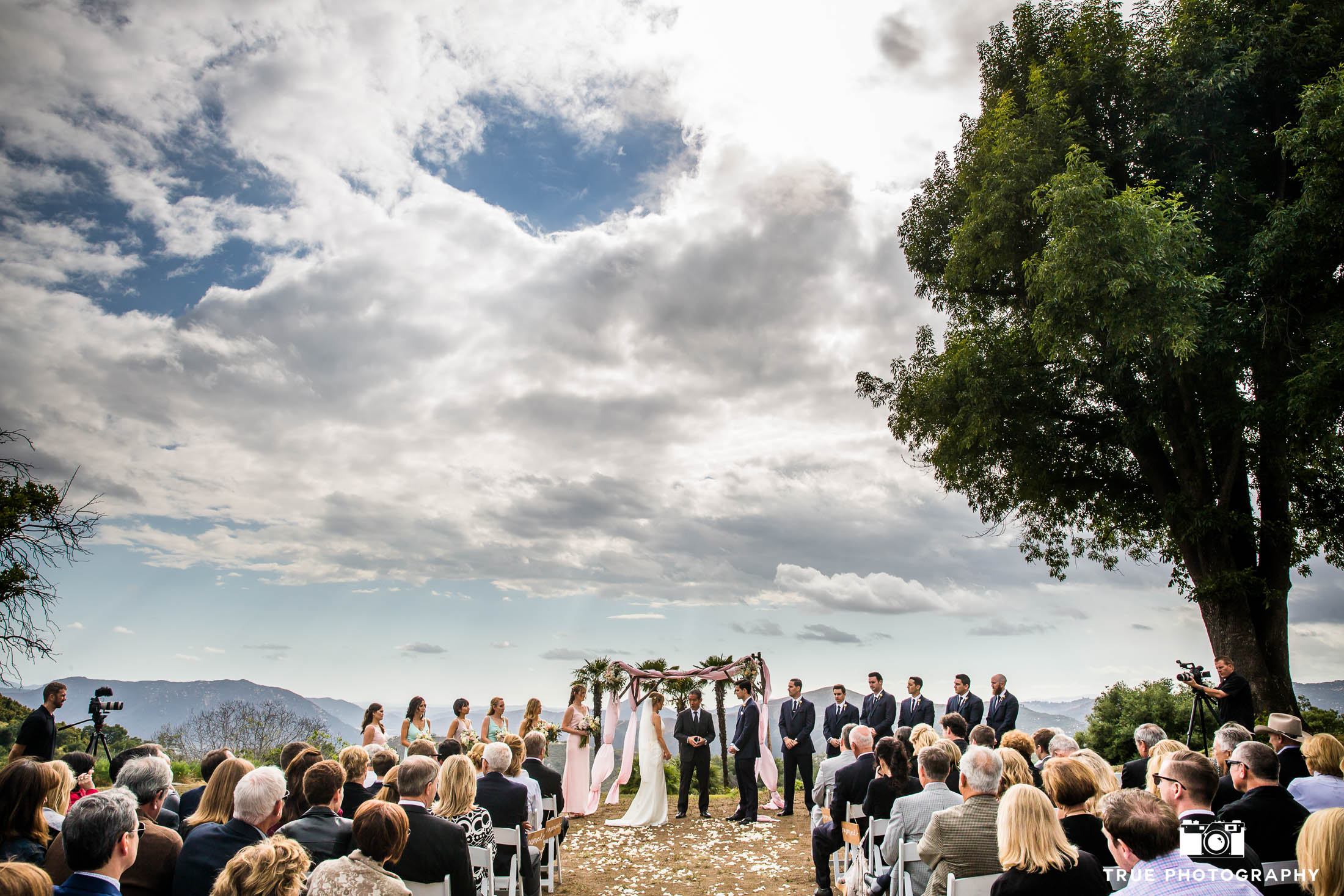 Wide-angle perspective of bride and groom tying the knot during rustic outdoor wedding ceremony