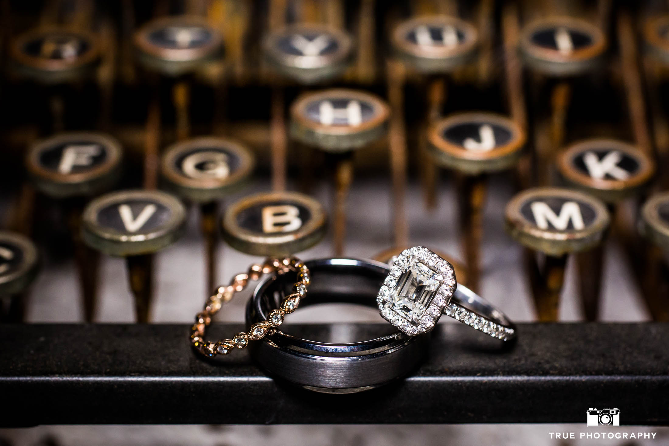 Bride and Groom's ornate diamond rings placed on vintage typewriter at rustic ranch wedding