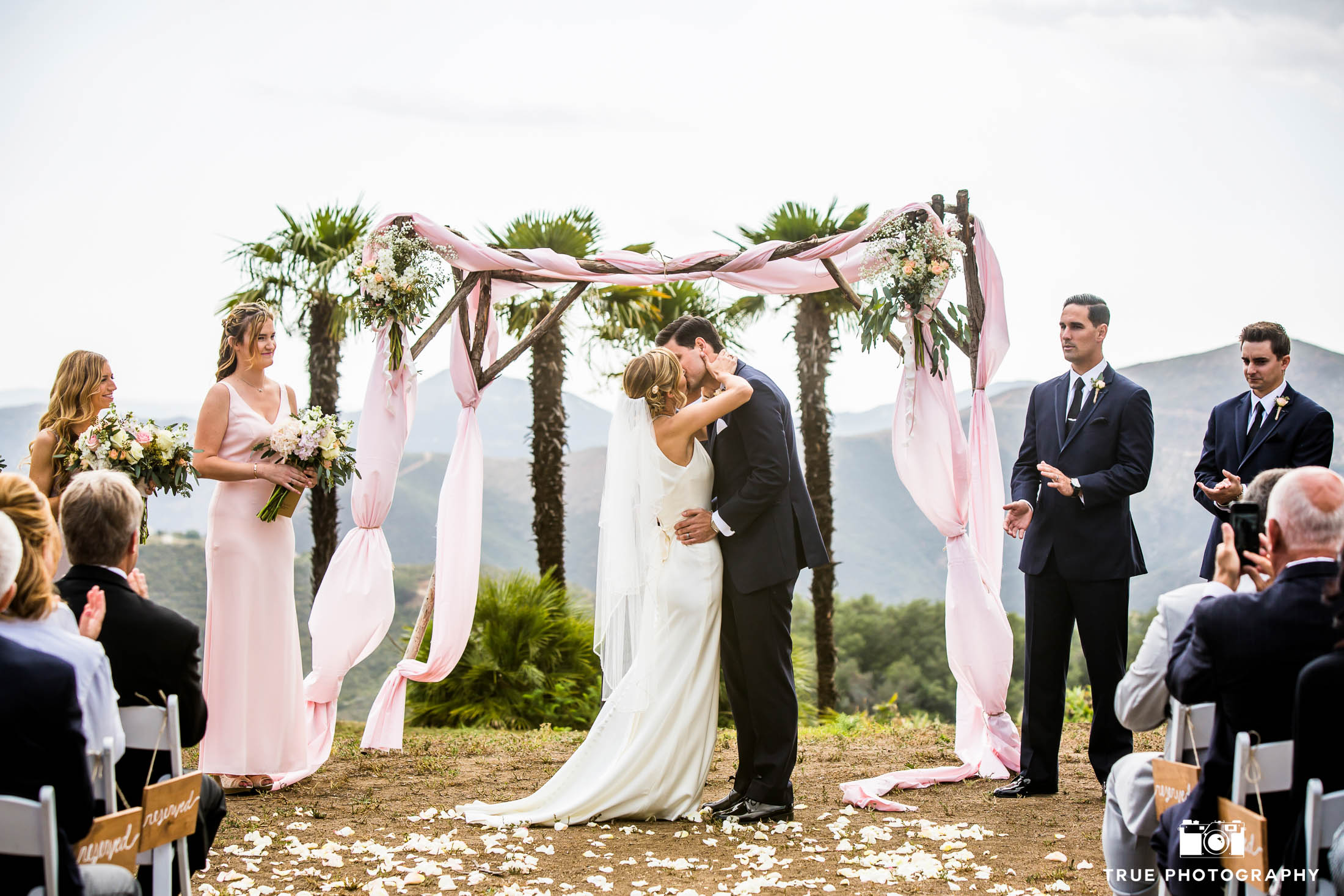 Groom dips Bride during First Kiss at outdoor wedding ceremony overlooking mountains