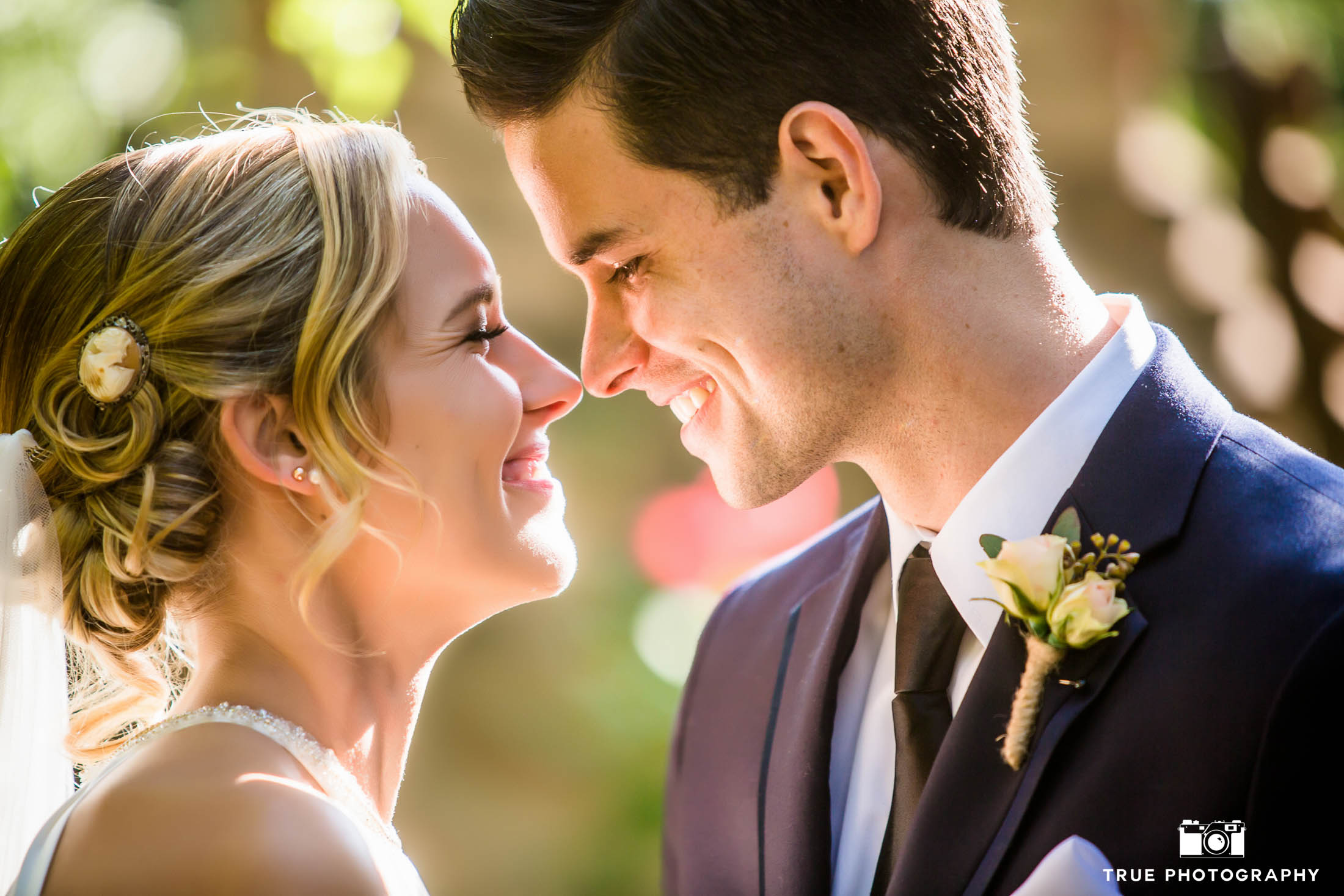 Romantic bride and groom look into each other's eyes and touch noses