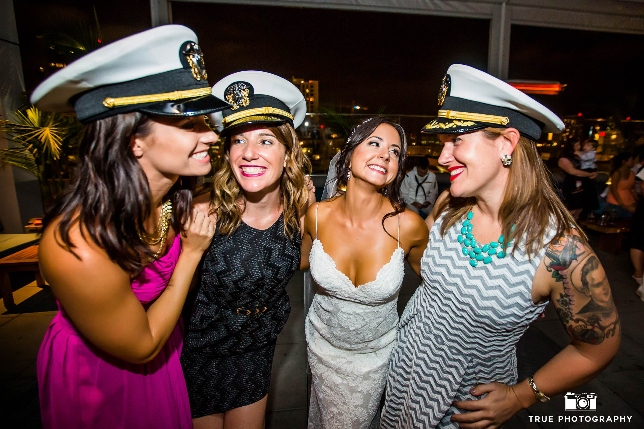 Bride poses with wedding guests as they laugh while wearing navy military hats