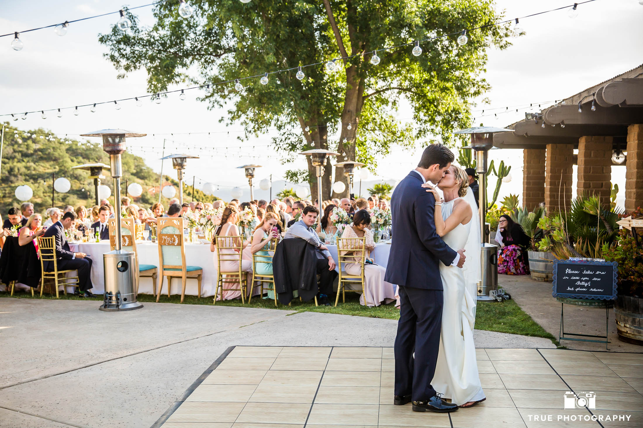 Bride and Groom share romantic First Dance during rustic outdoor wedding reception