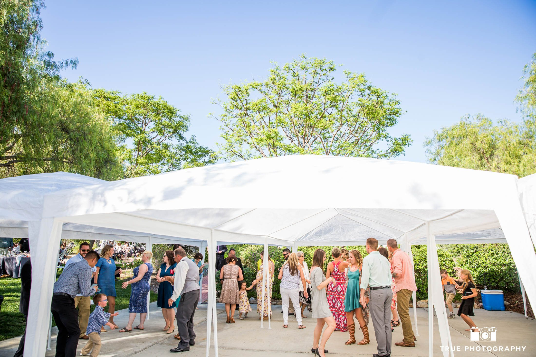 Wedding guests have fun dancing under tent at outdoor wedding reception