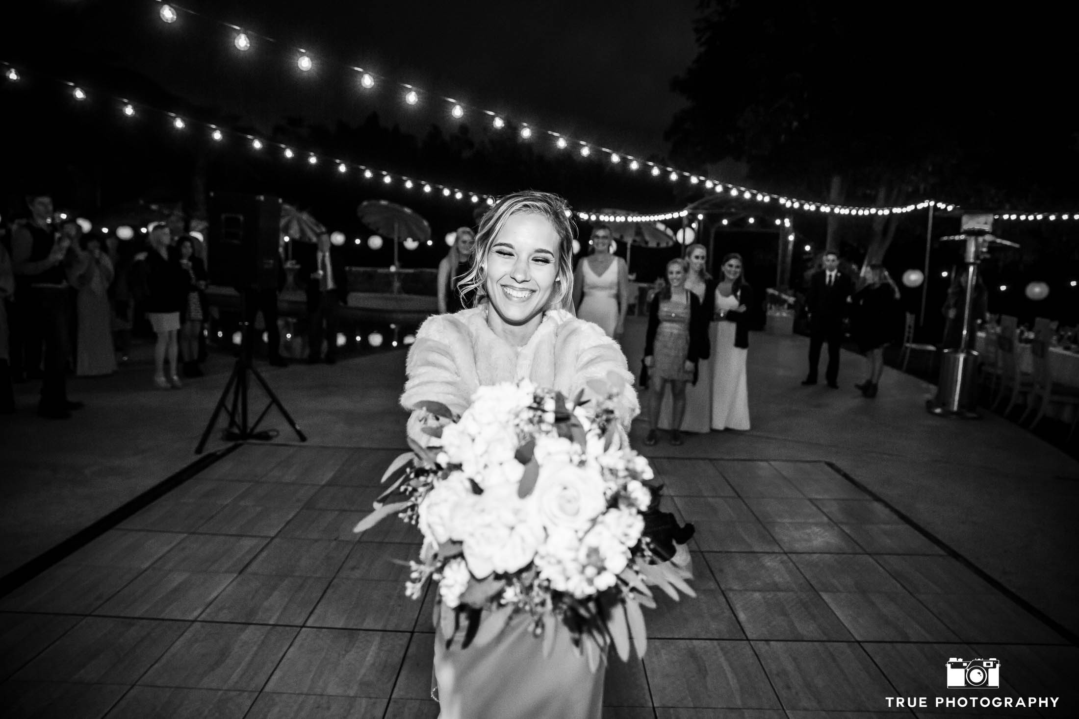 Bride prepares to toss bouquet during outdoor reception