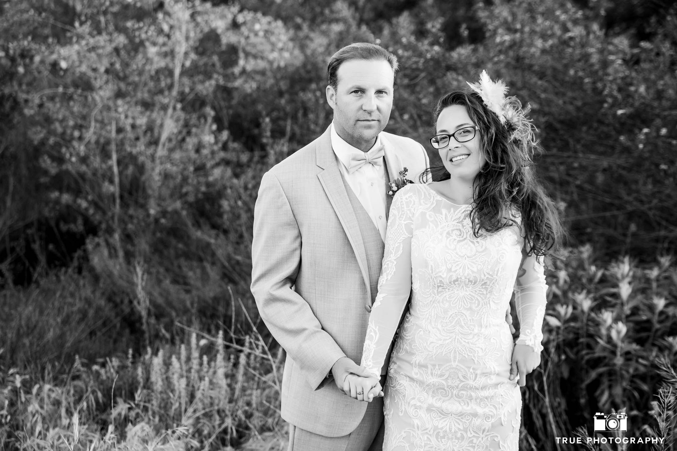 Black and White photo of Bride and Groom standing in grassy field on wedding day
