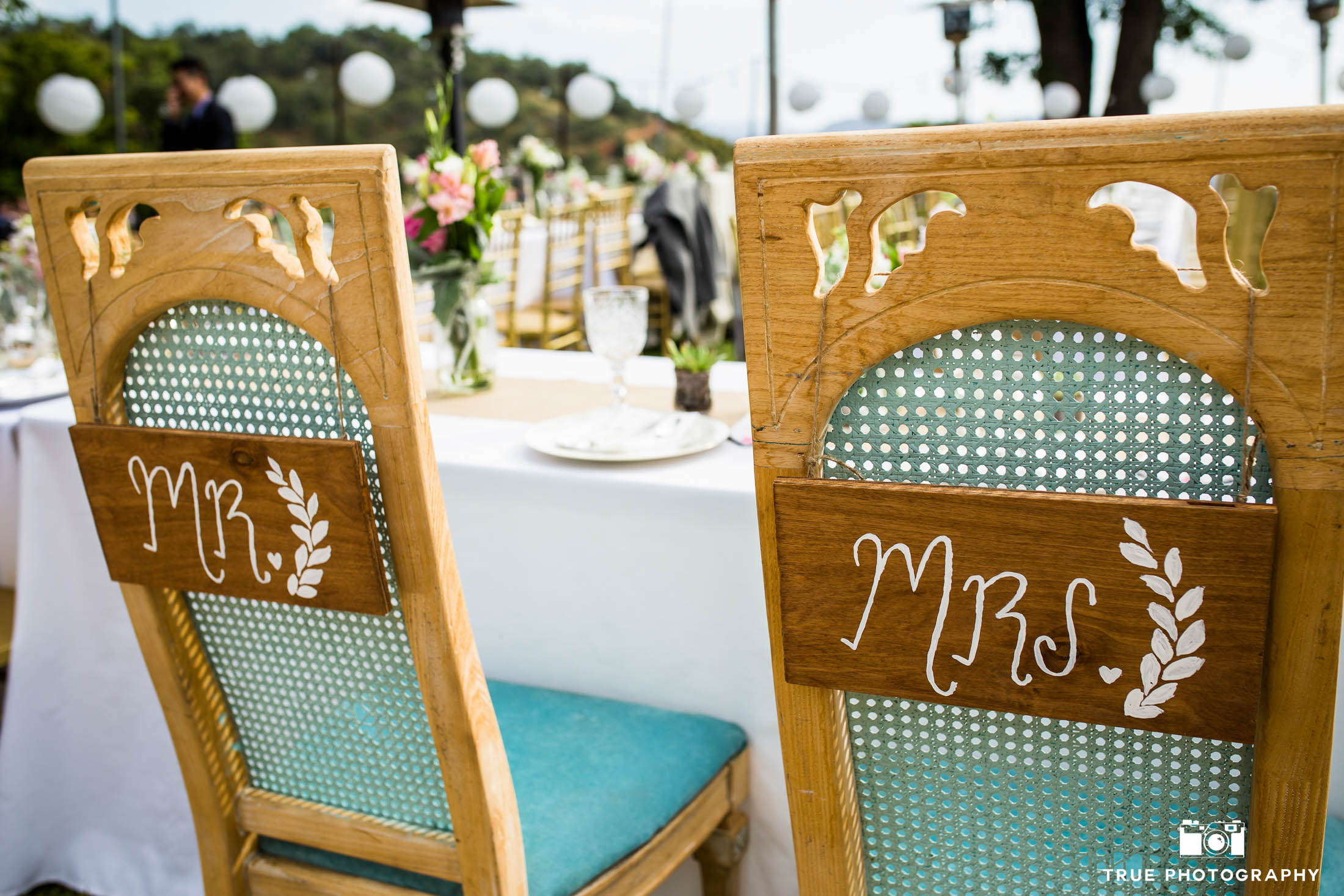 Custom rustic wicker chairs for bride and groom during outdoor reception