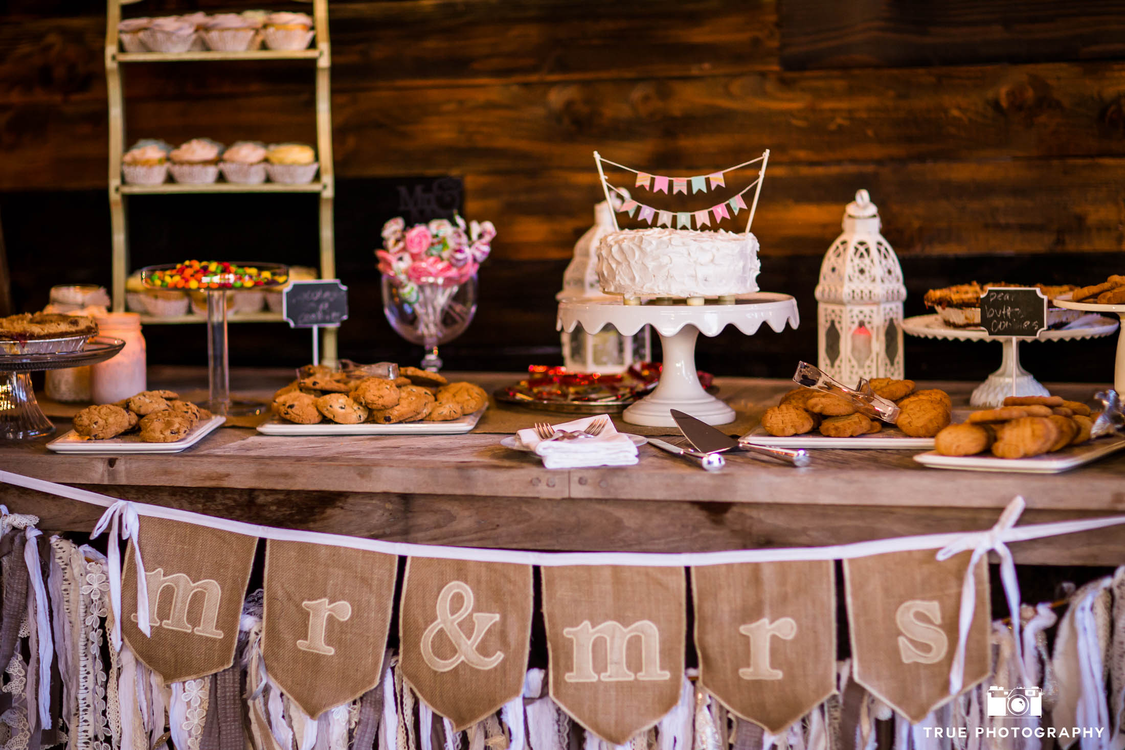 Dessert table with wedding cake, cookies and candy during rustic wedding reception