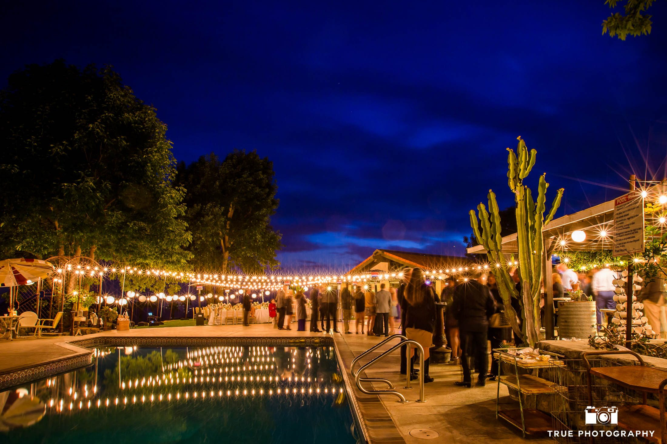 Creative long-exposure of outdoor rustic wedding reception on ranch at night