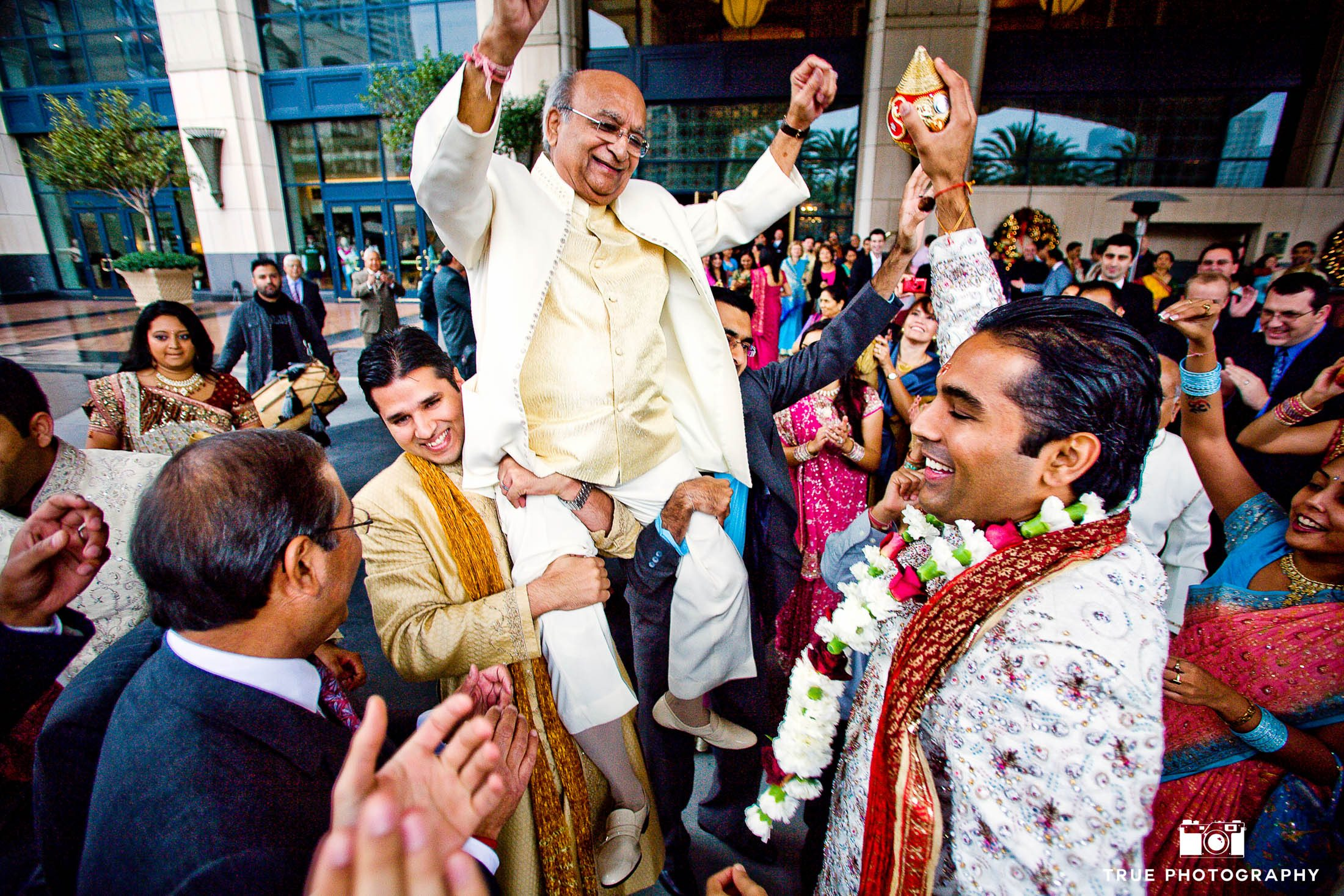 Guests lift up Groom's Father during Indian wedding
