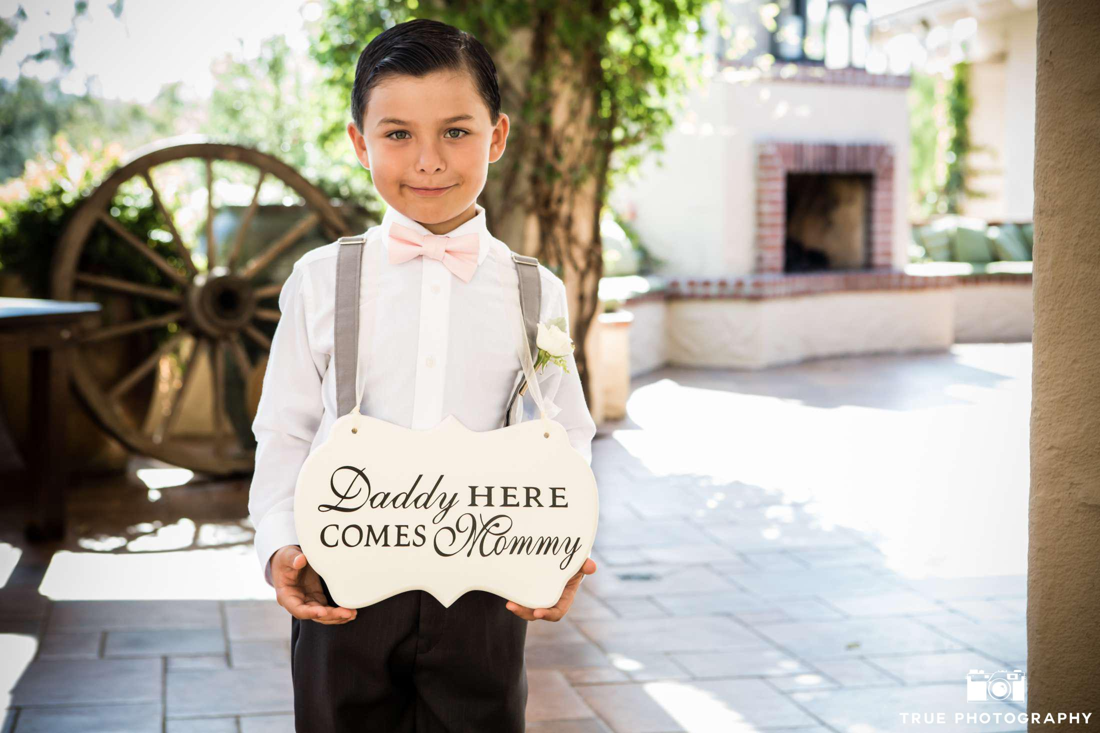 ring bearer in pink bow tie with sign
