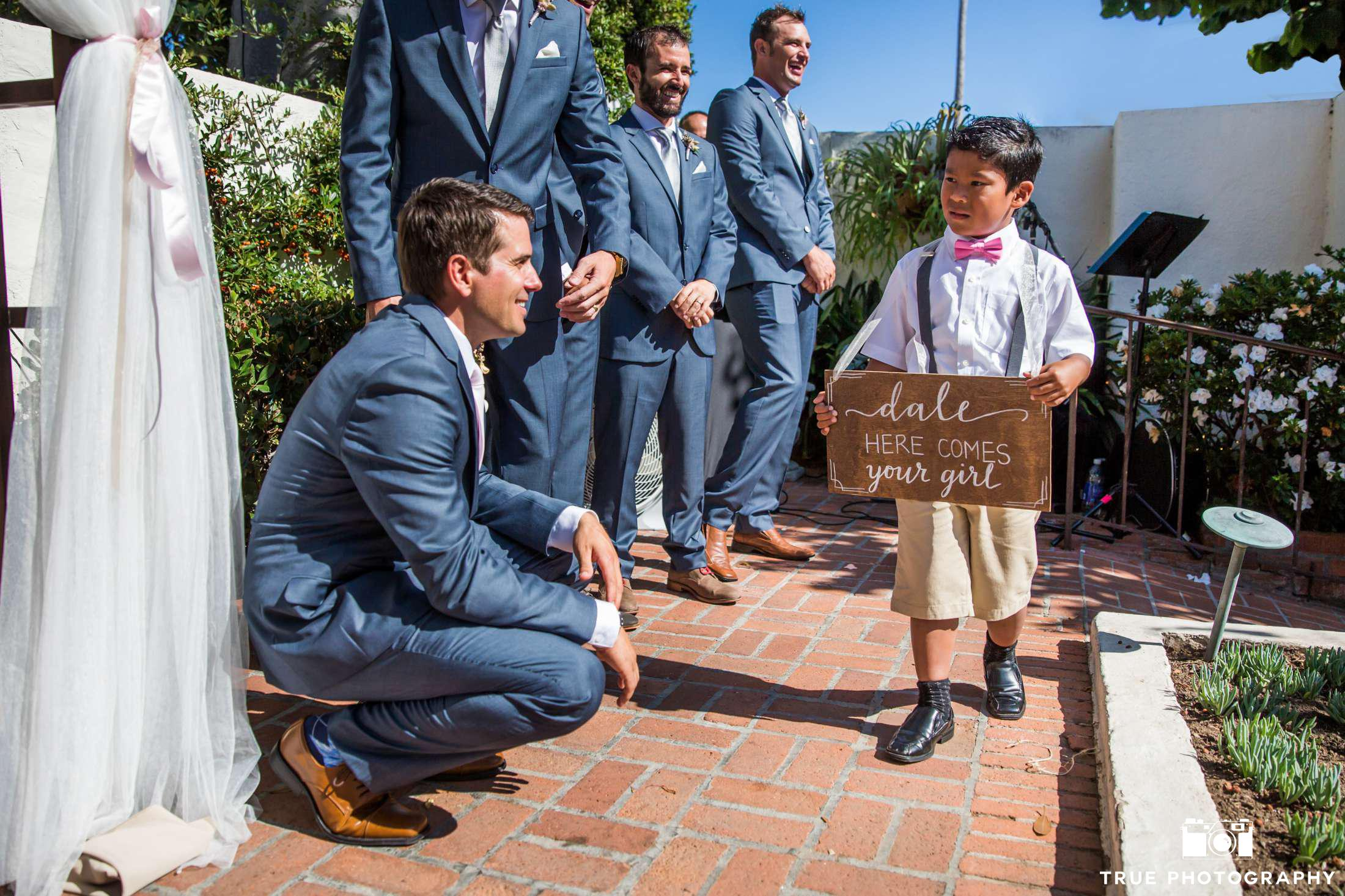 kneeling groom with ring bearer holding sign