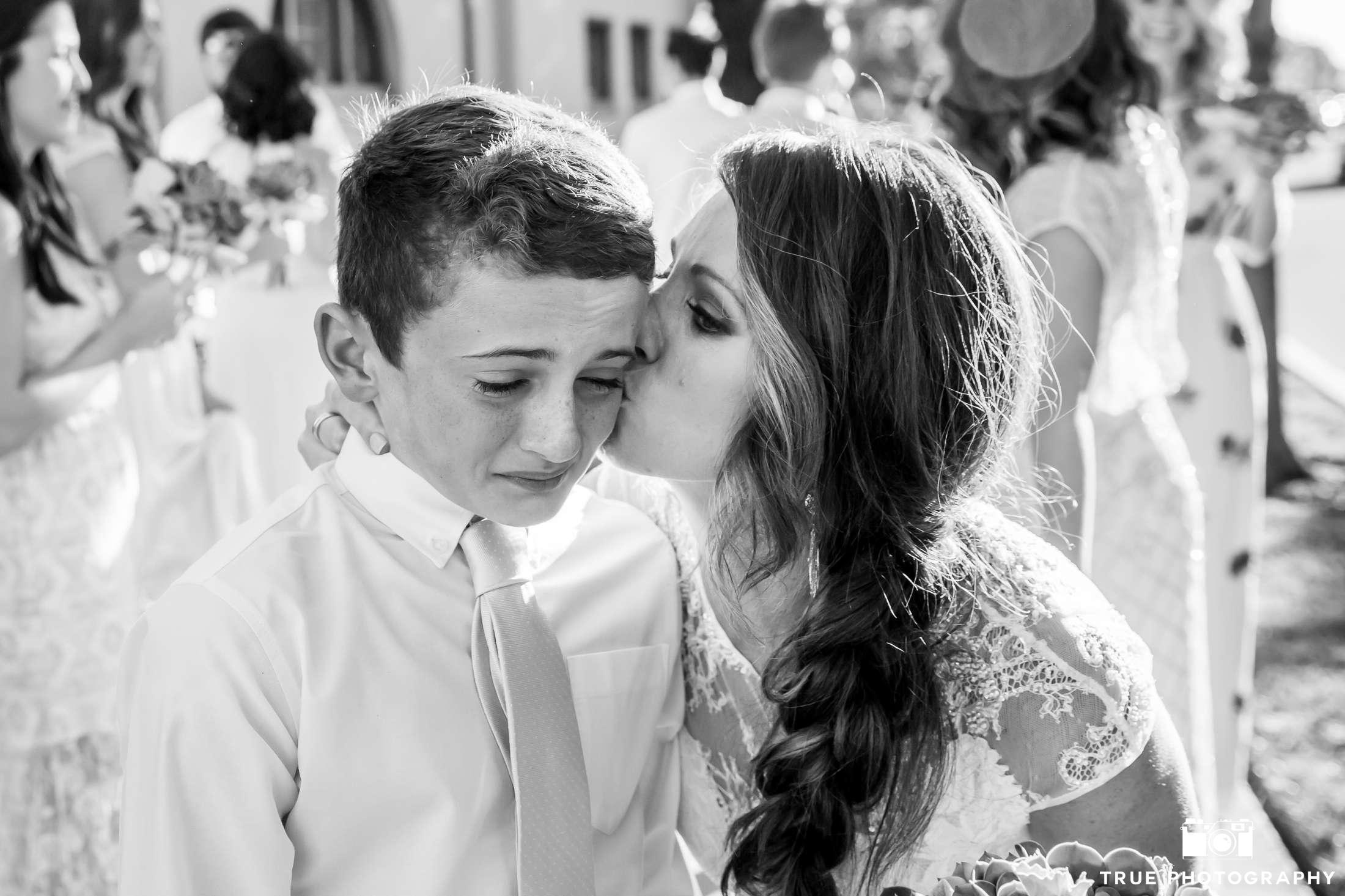 bride kissing embarrassed ring bearer