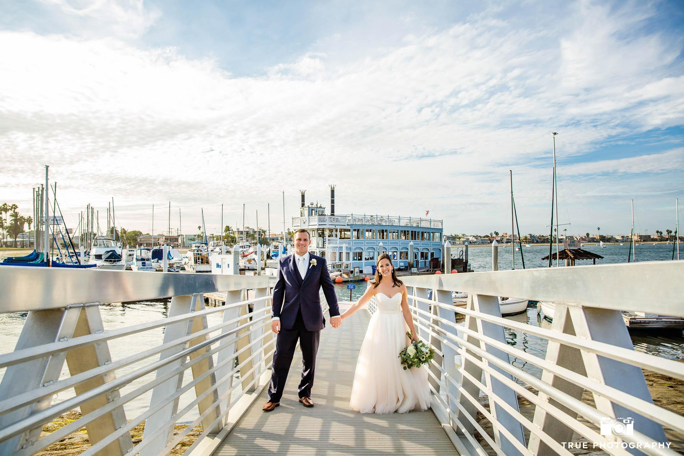Bride and Groom hold hands on bridge at Bahia Resort