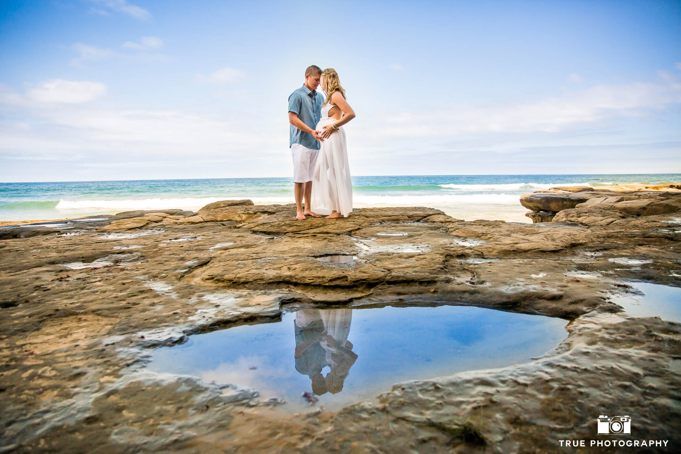 Expecting couple embraces during beach maternity