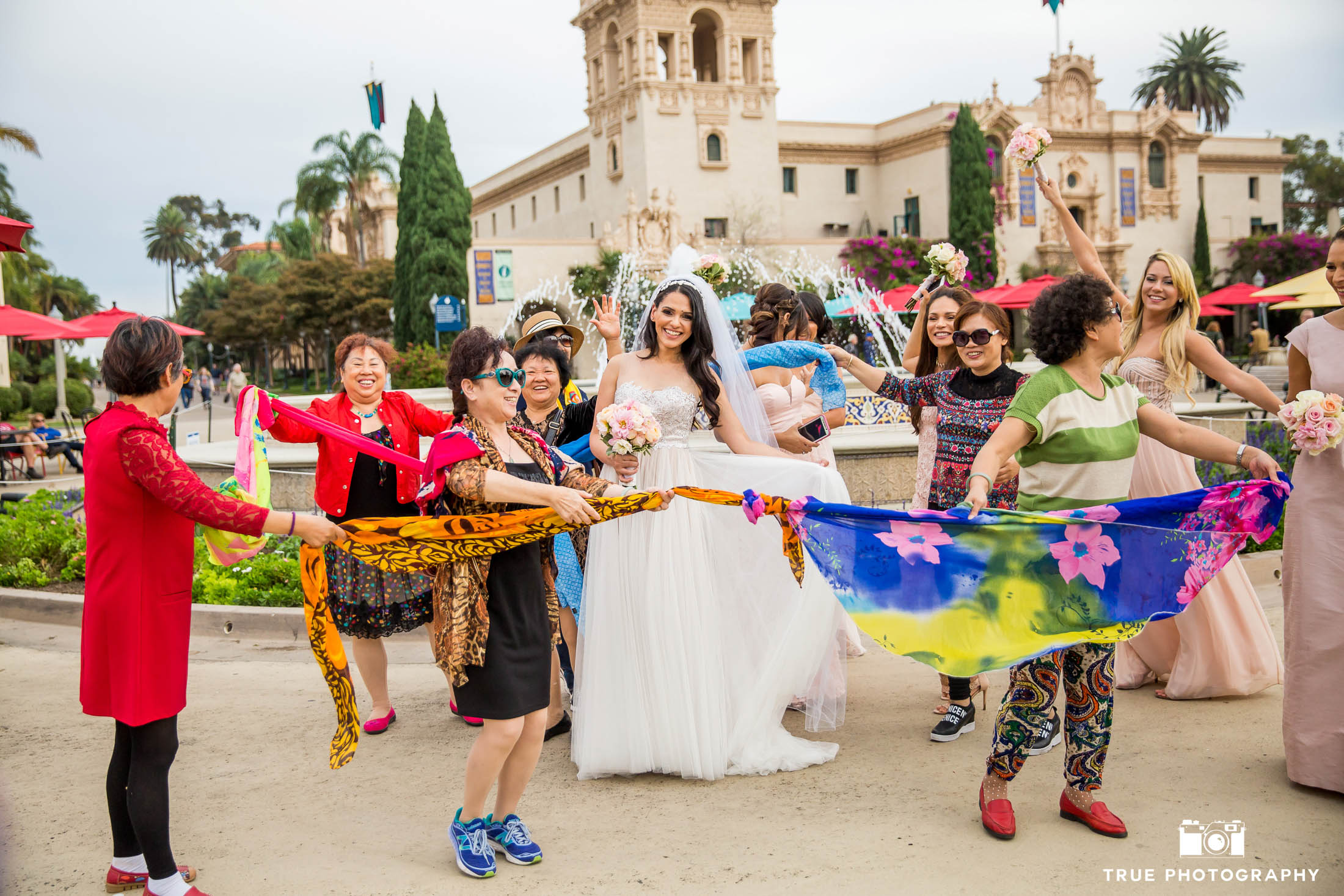 Street performers dance with scarves around Bride after wedding ceremony