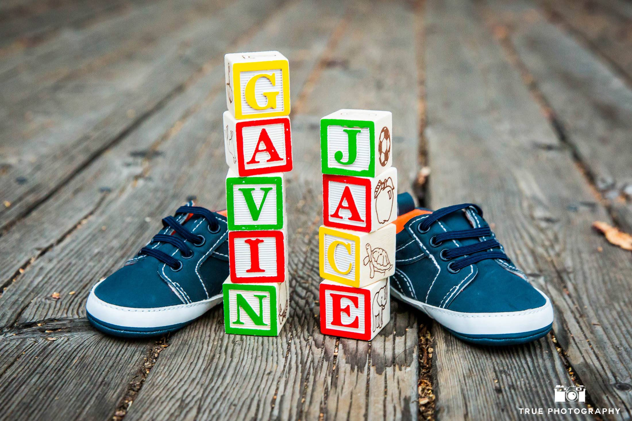 Baby shoes frame letter blocks during maternity session
