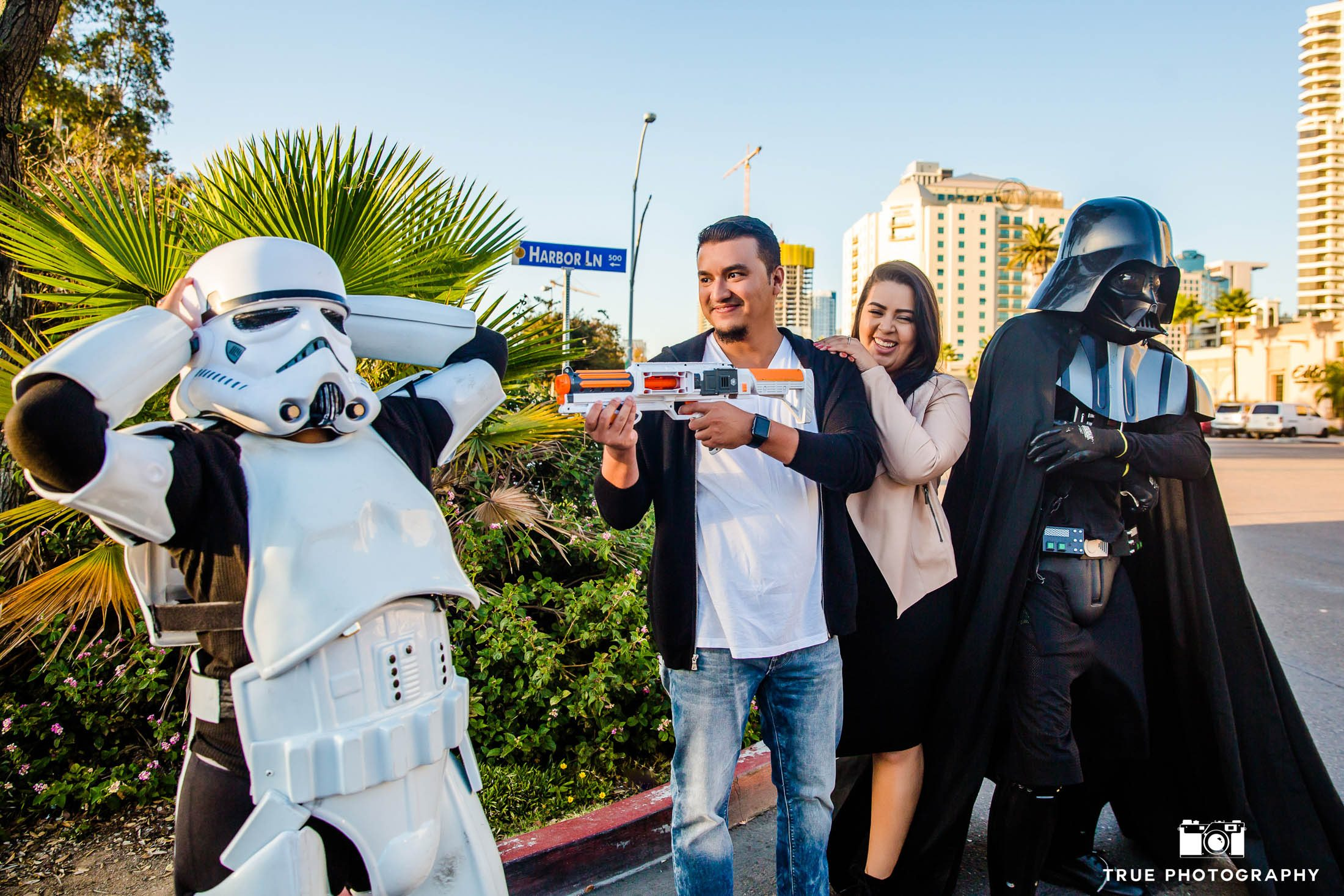Engaged couple have fun playing with Star Wars characters in Downtown San Diego