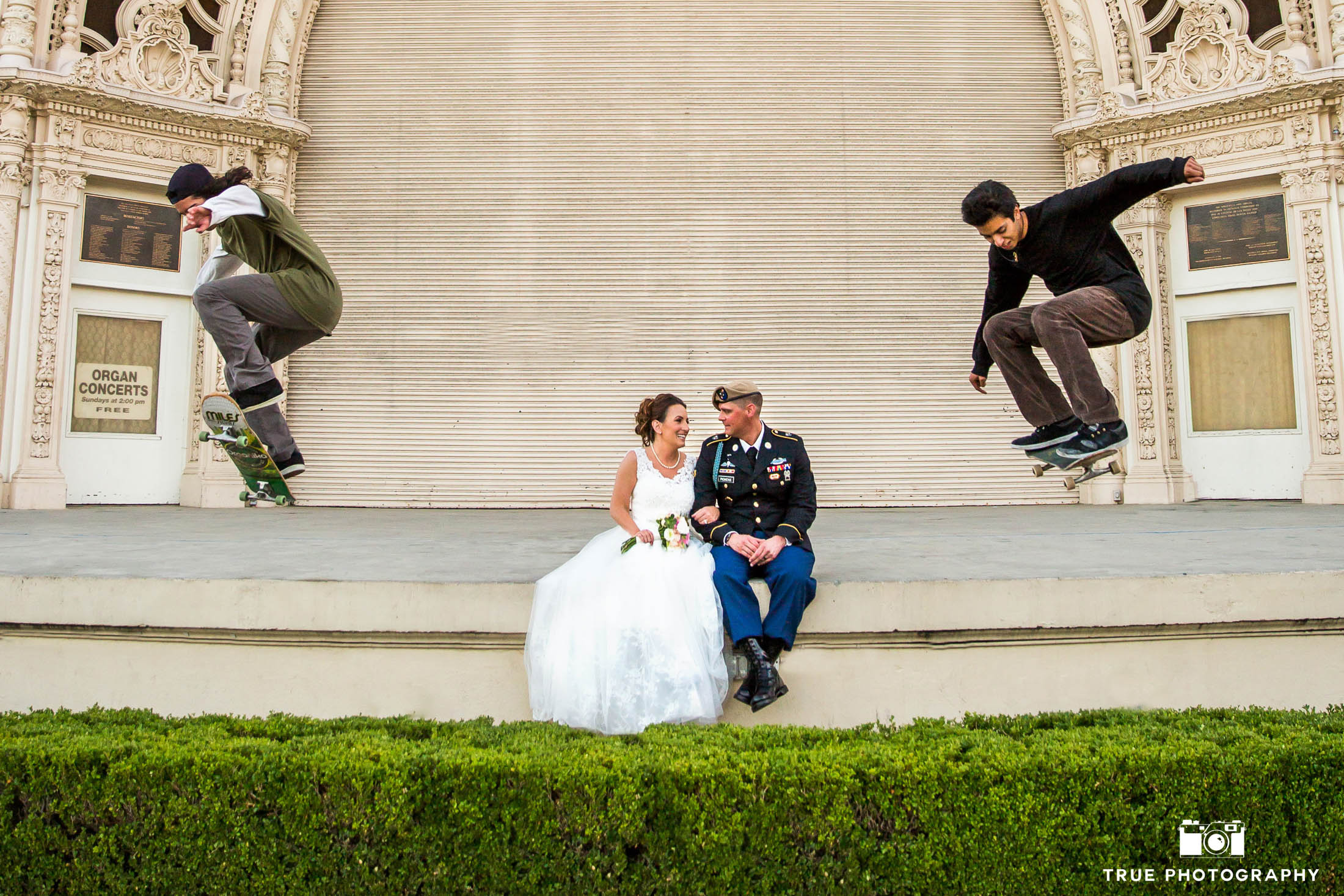 Bride and Groom sit on ledge as skateboards do tricks around them