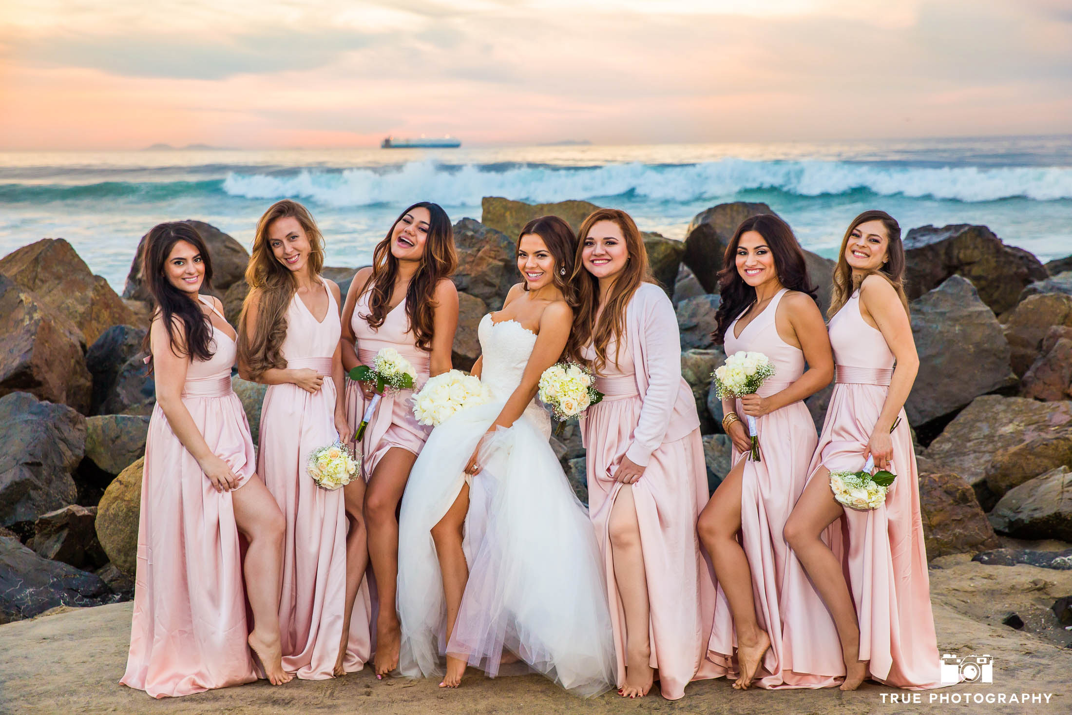 Bridesmaid have fun showing off legs in pink dresses by David's Bridal