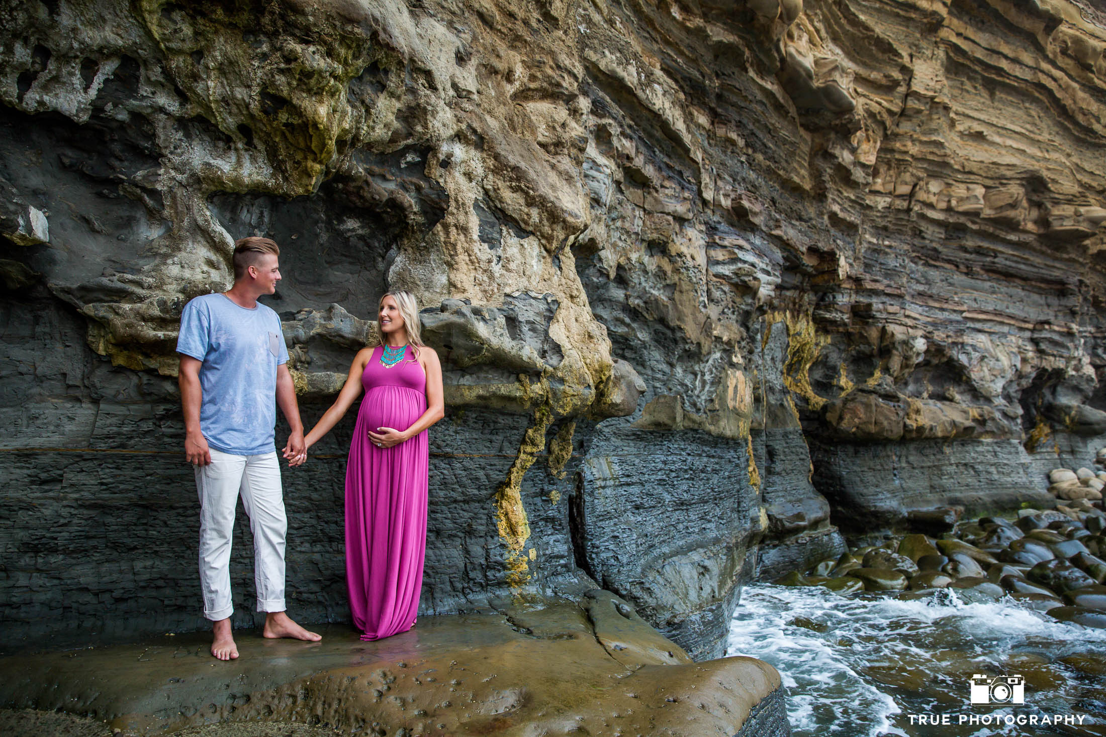 Husband and Wife look at one another and hold hands during maternity session at Sunset Cliffs