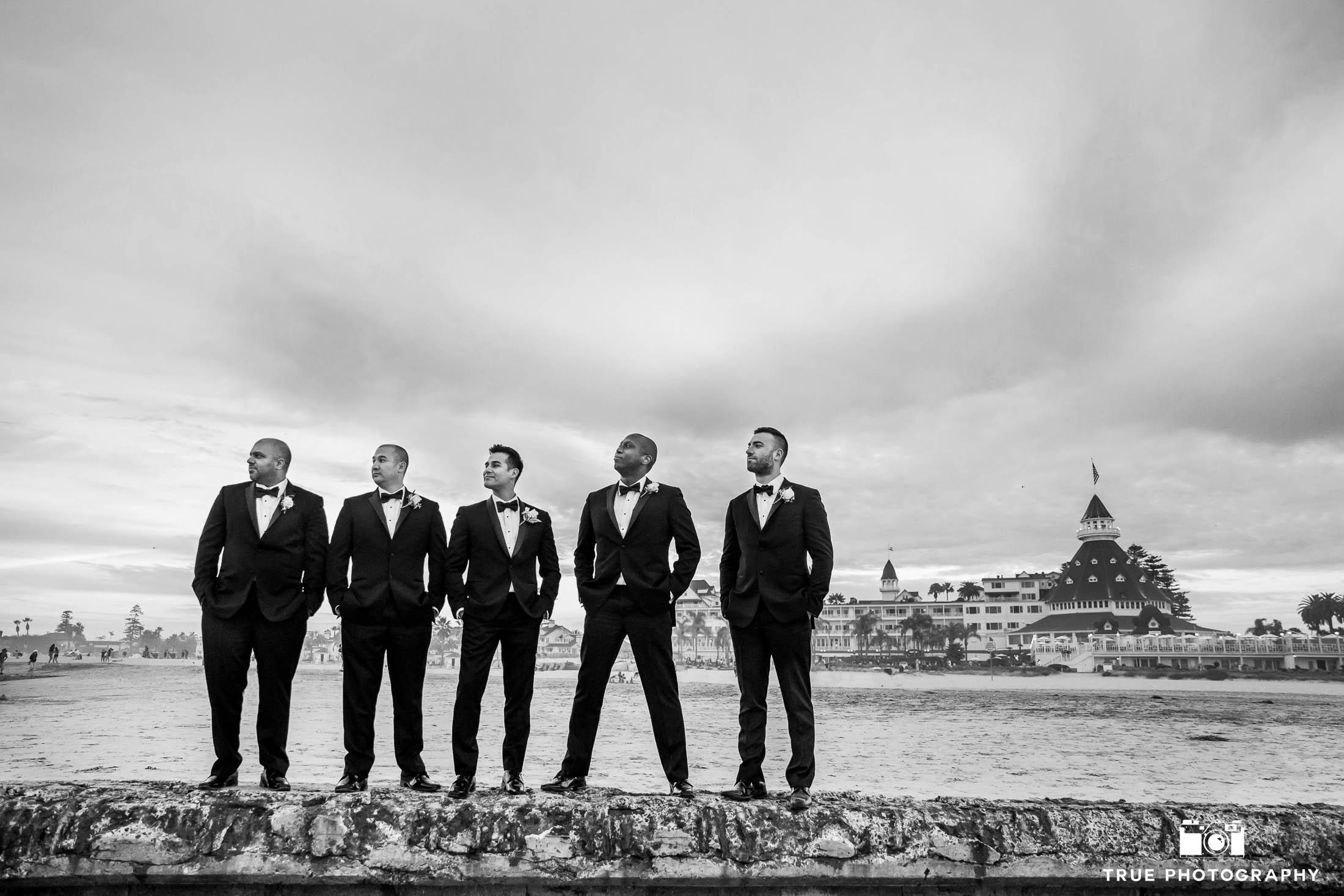 Groom and Groomsmen stand on sea wall at Hotel Del Coronado