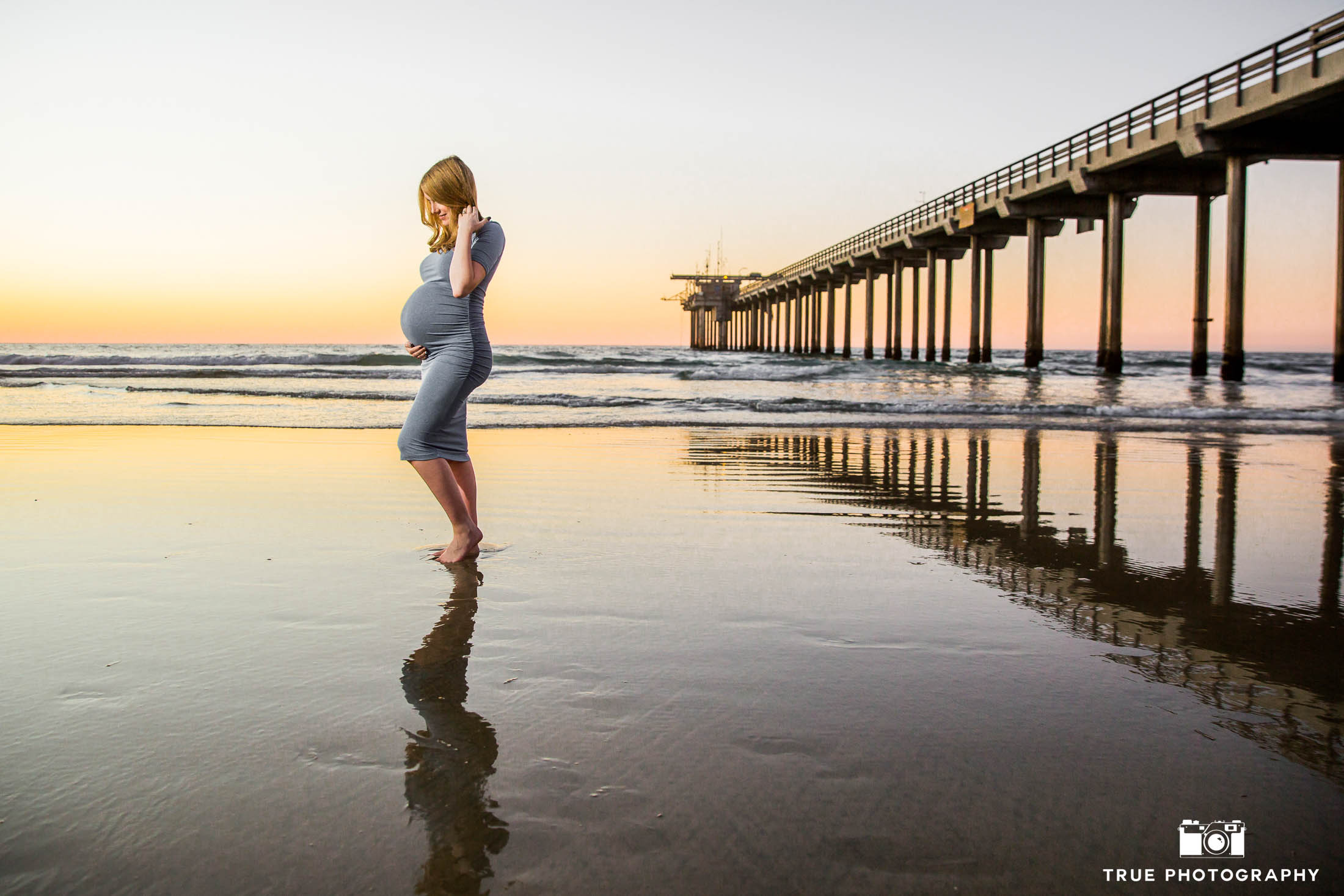 Expecting mother holds belly next to Scripps Pier