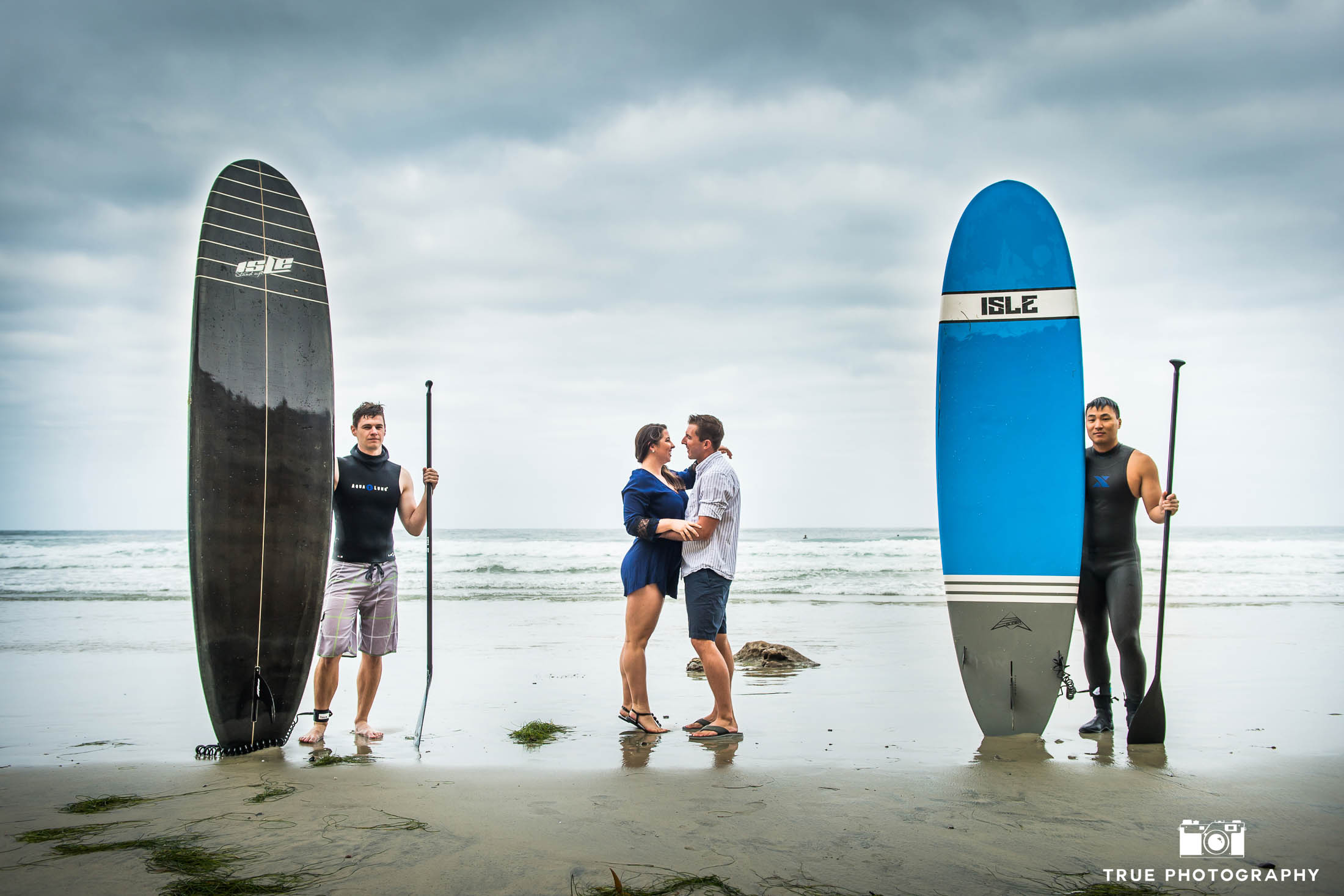 Engaged couple kiss on beach between two surfers