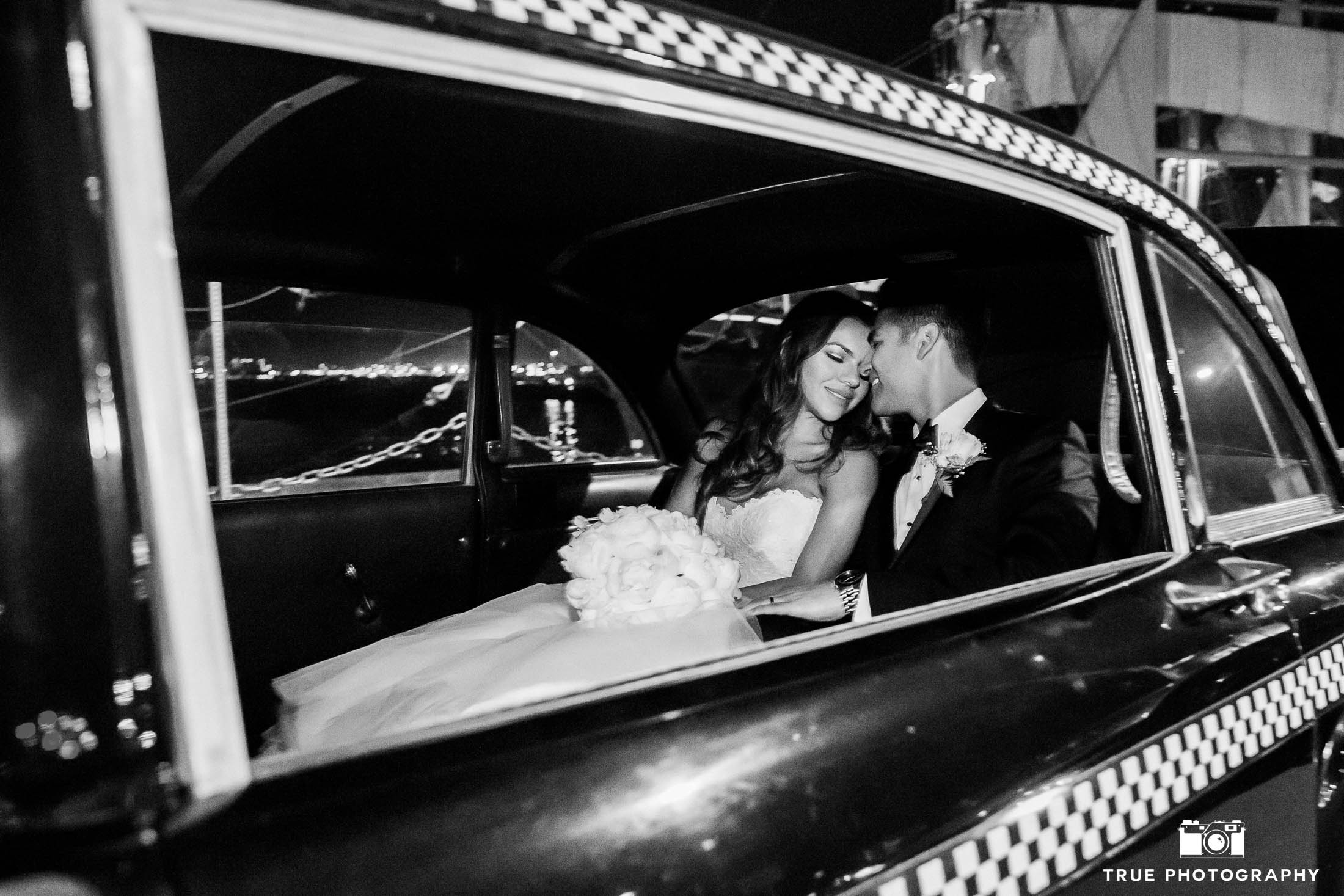 Black and white photo of bride and groom embracing in vintage limo
