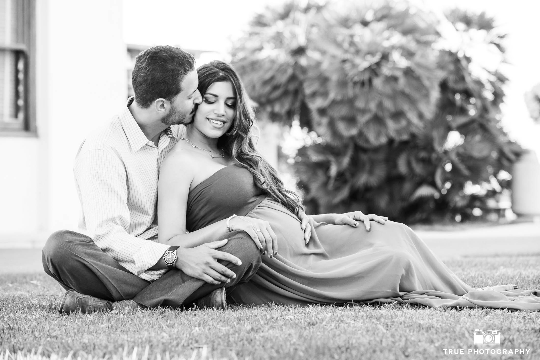 Expecting Couple sit on grass during maternity session
