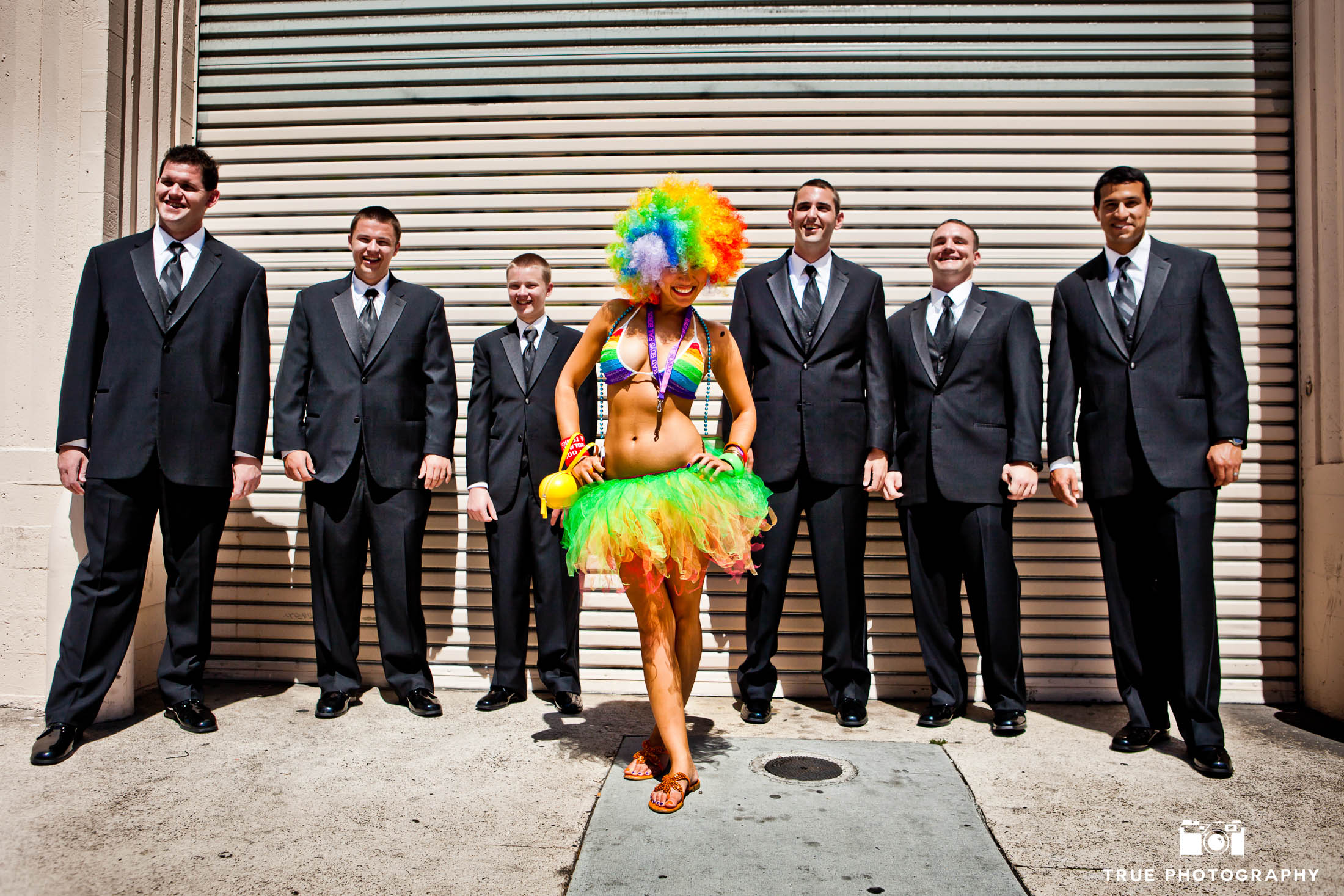 Groomsmen laugh behind colorful street performer