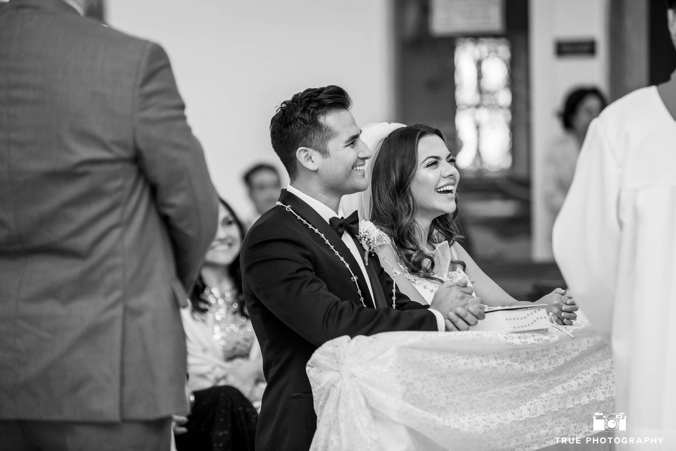 Bride and Groom laughing during church ceremony