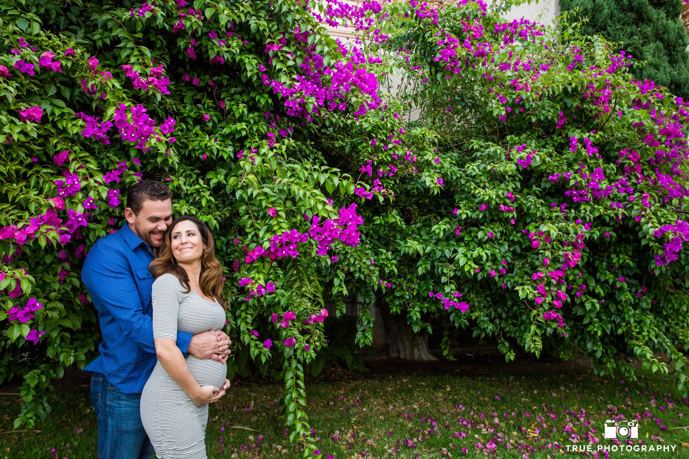 Husband and Wife embrace and laugh during cute maternity session