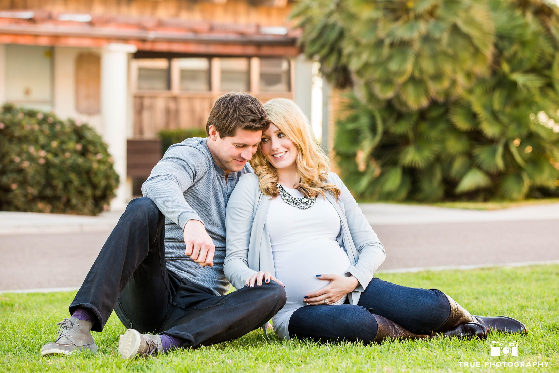 Married couple sit on grass during maternity session