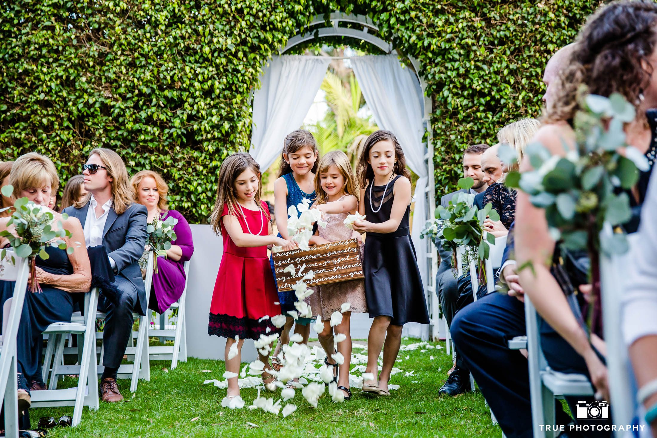 Cute flowergirls throw flowers down aisle at wedding