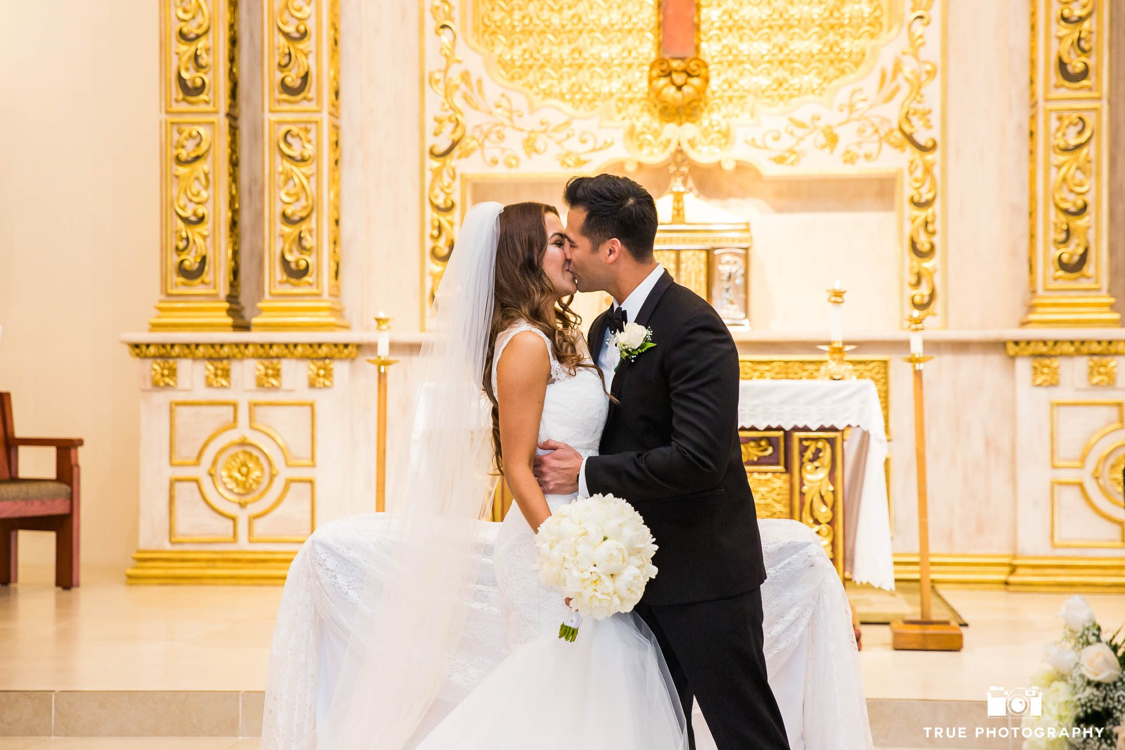 Bride and Groom share romantic First Kiss during Catholic church ceremony at Our Lady of Guadalupe in Chula Vista
