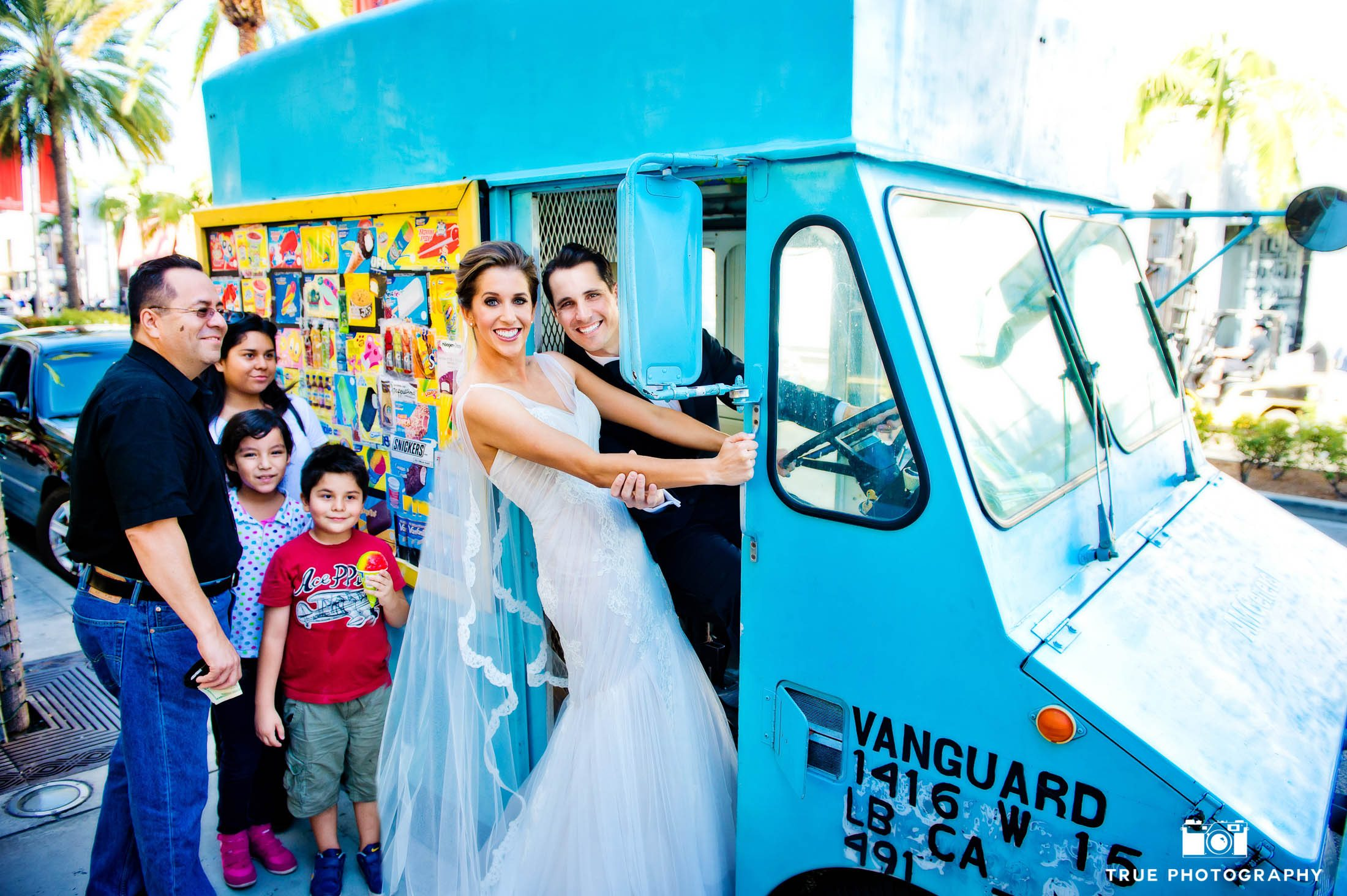 Bride and Groom stand in door of ice cream truck after wedding ceremony