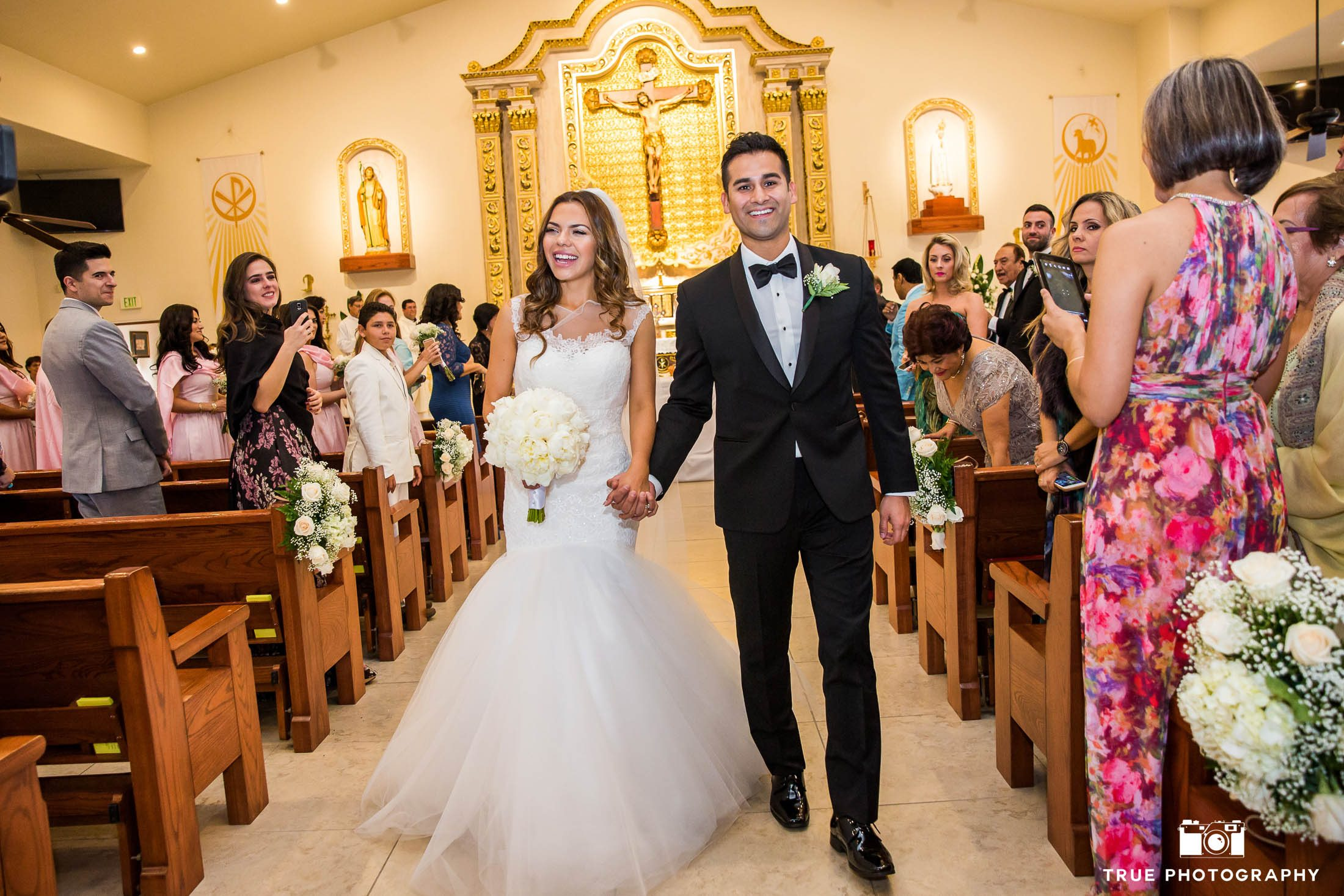 Bride and Groom's candid smiles as they walk down aisle after first kiss at Our Lady of Guadalupe church