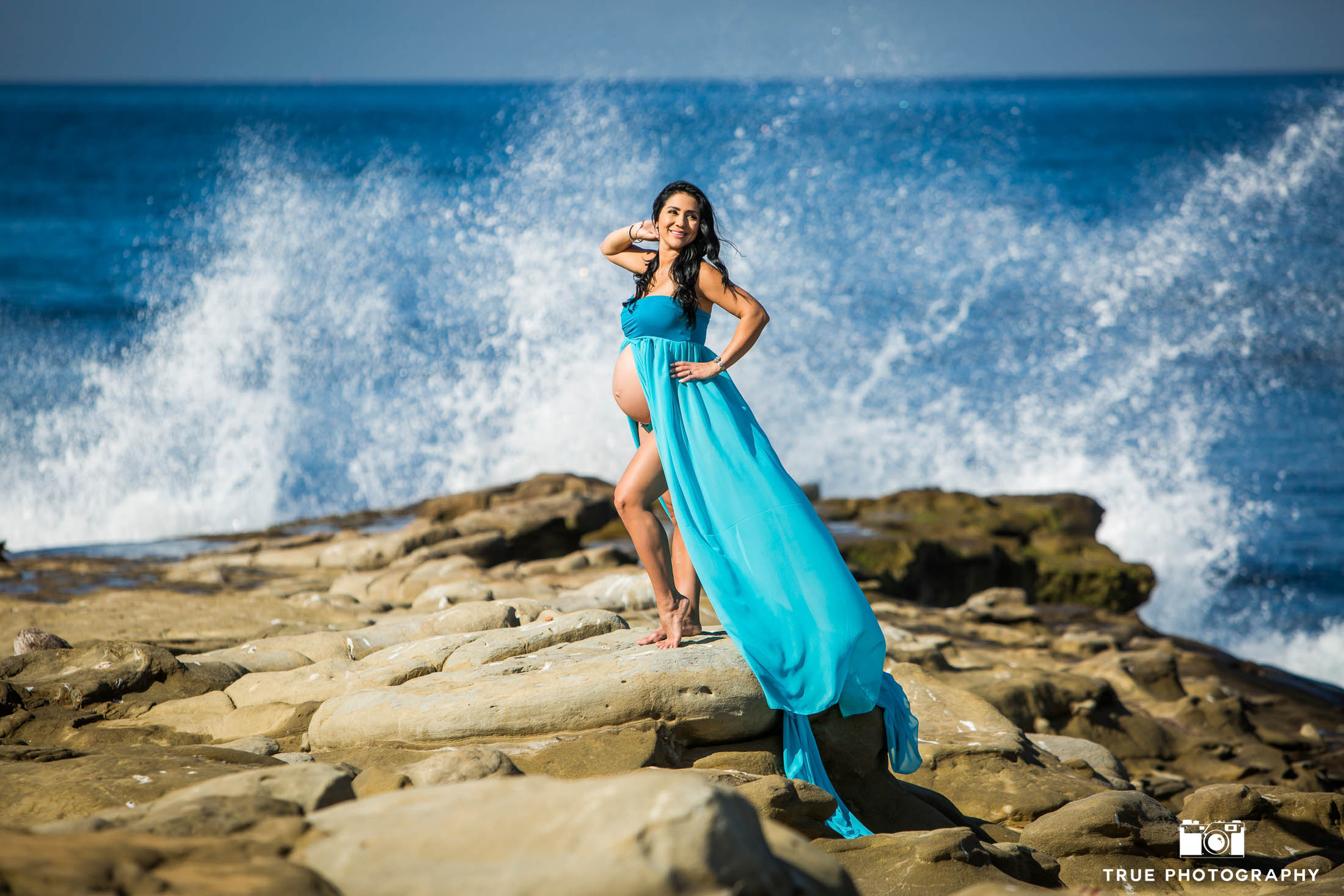 Expecting mother in blue gown at beach