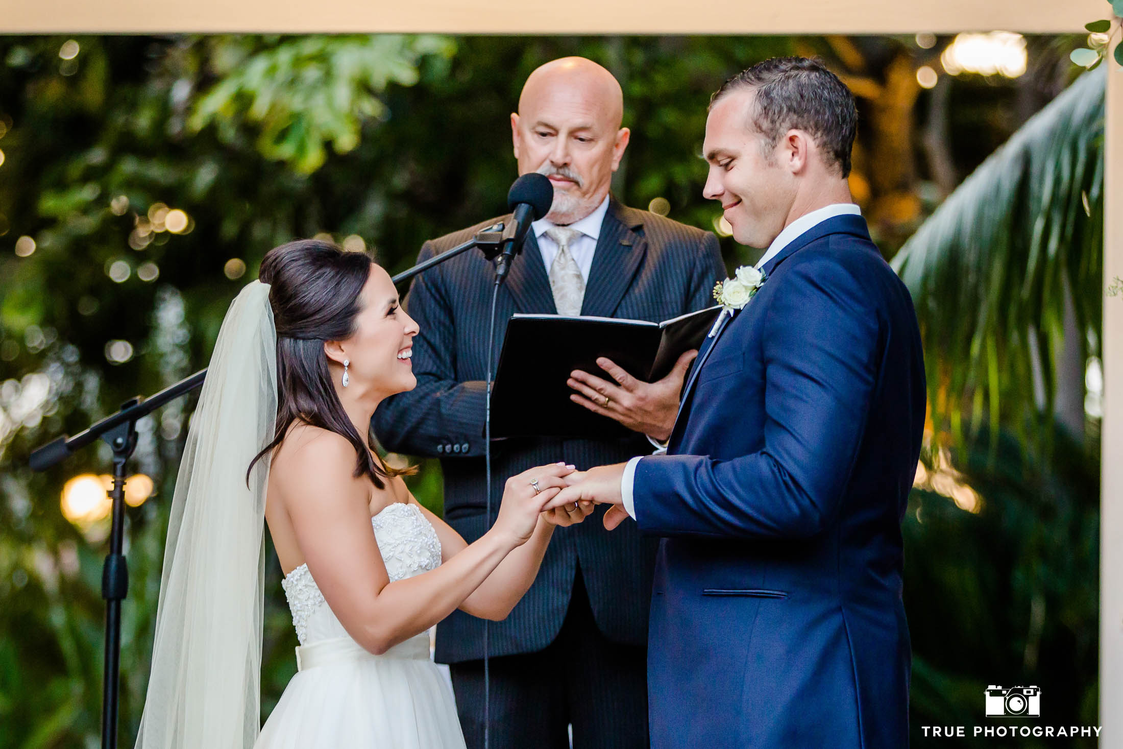 Bride places wedding ring on groom's hand